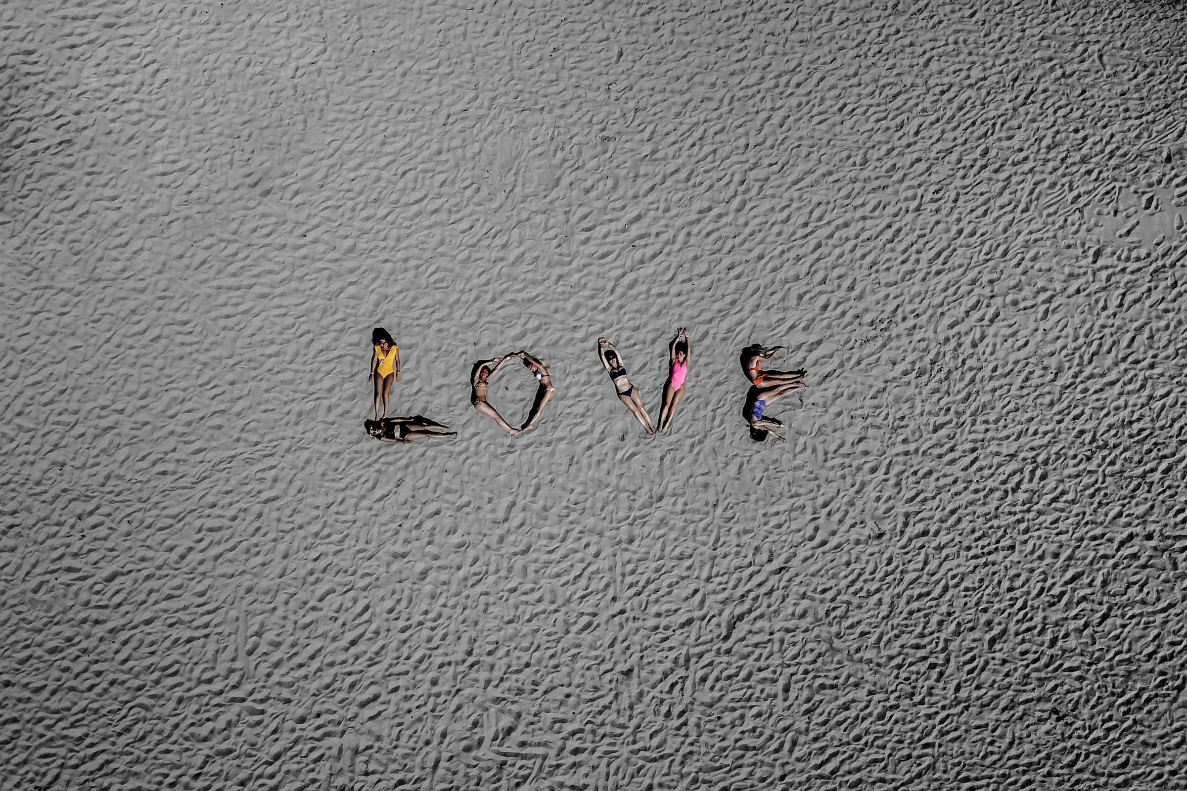 Wedding party spells out Love on sandy beach - photo by Julien Laurent Georges