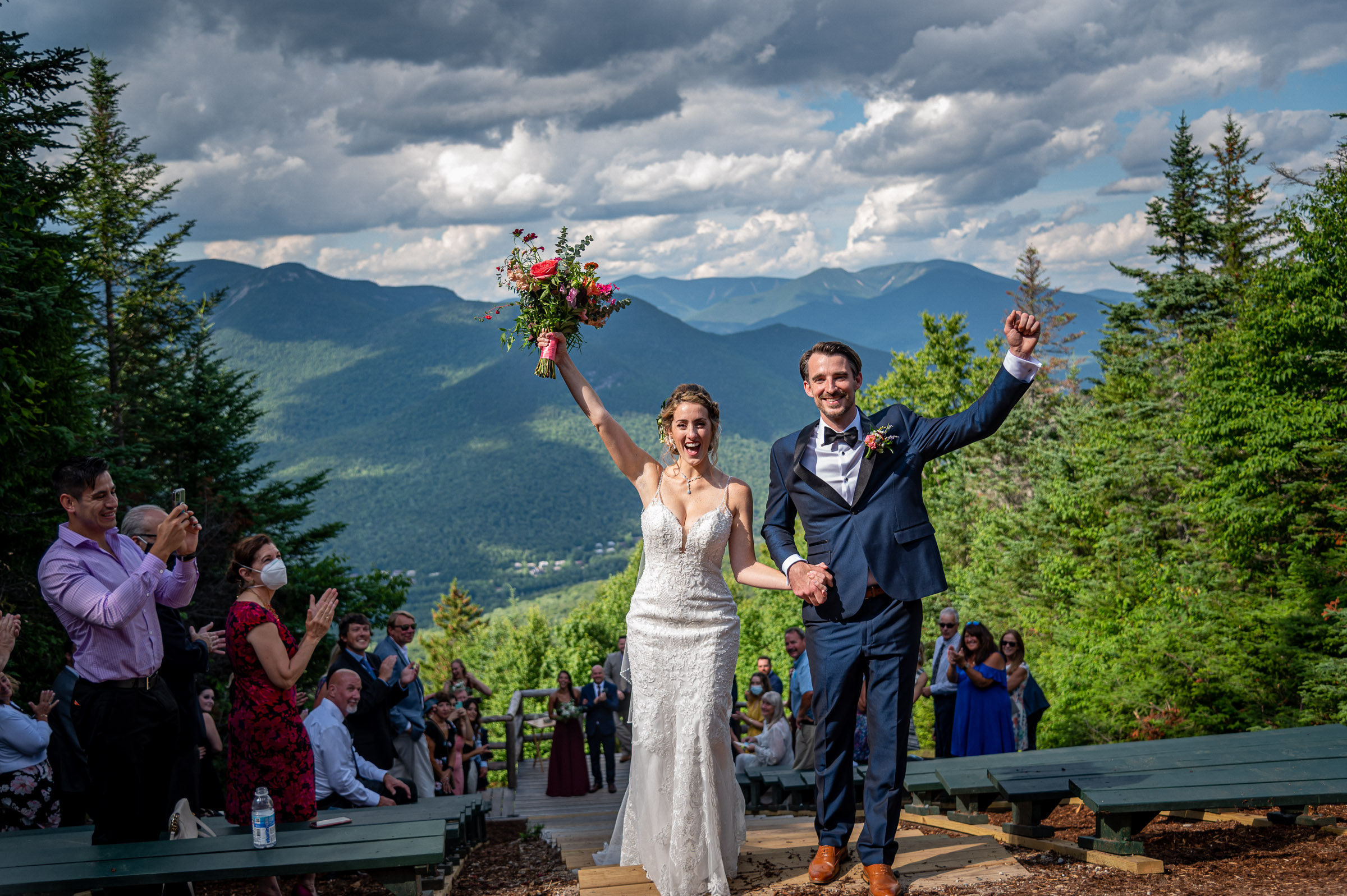 happy-couple-recessional-against-against-well-wishers-clouds-and-mountains-randall-garnick-photography