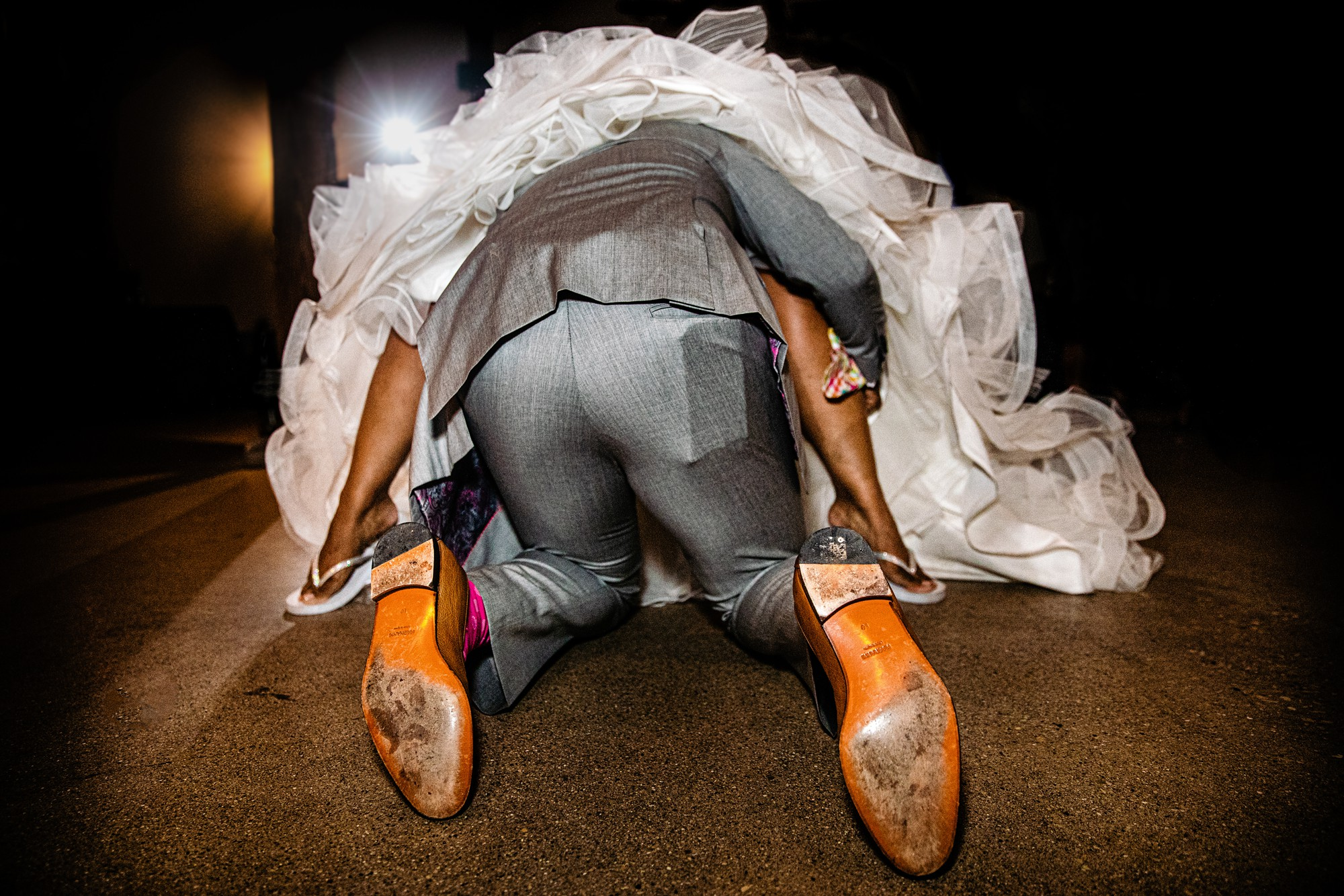 hilarious-wedding-photo-of-groom-diving-for-garter-by-yves-schepers-belgium-wedding-photographer