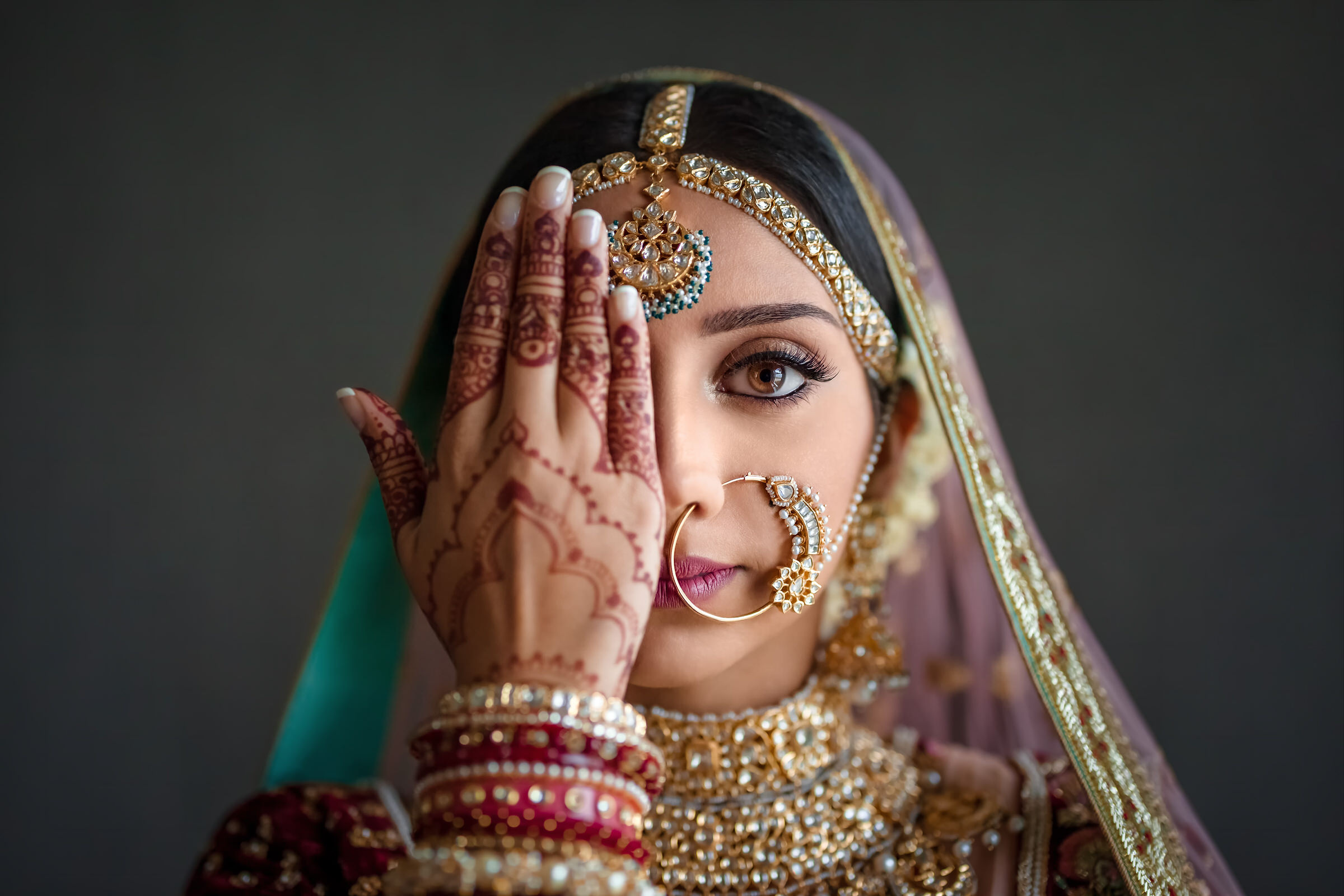 indian-bride-with-henna-hand-in-front-of-face-eye-jogia-photography