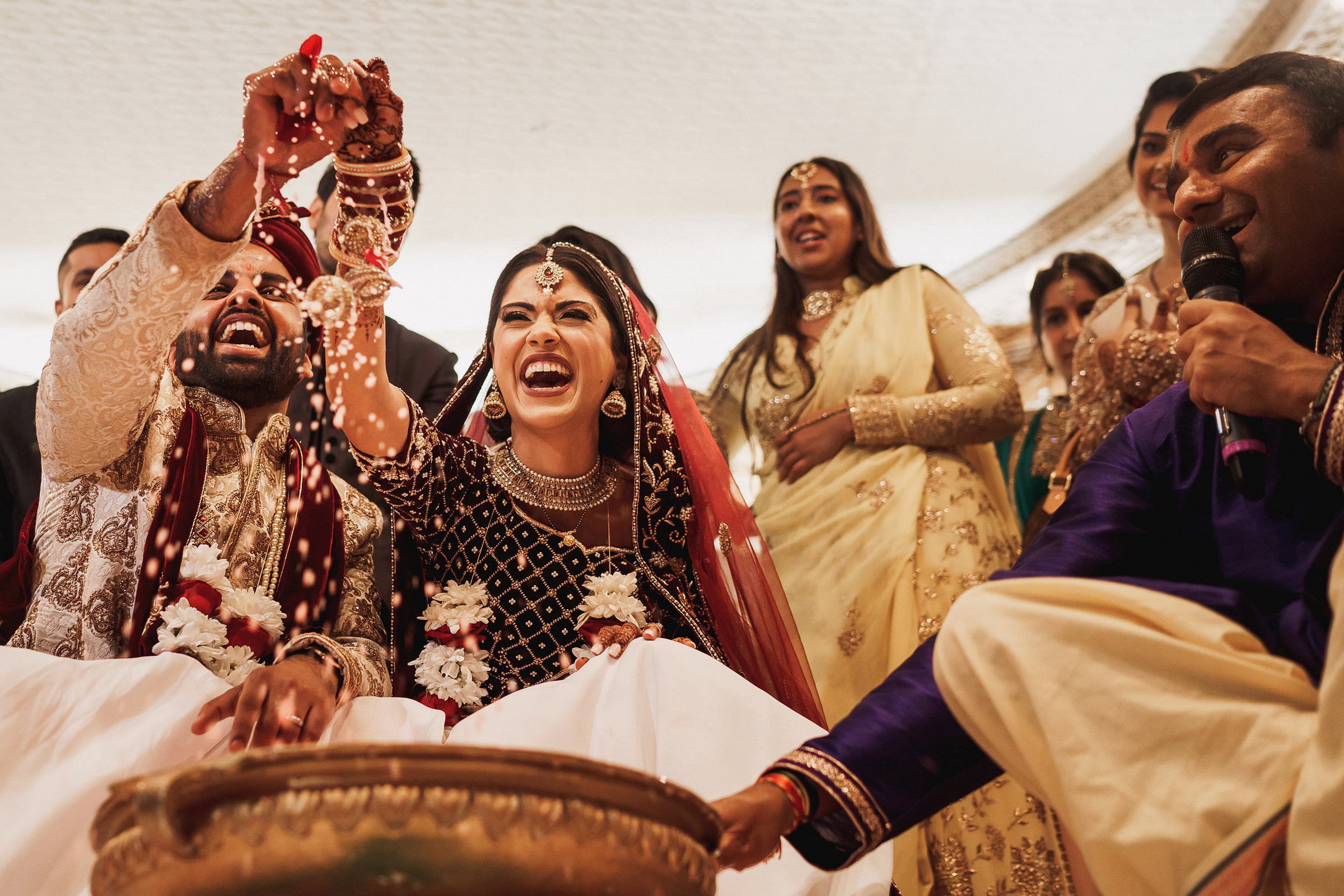 Joyful photo of Indian bride and groom during ceremony by f5 best London wedding photographr