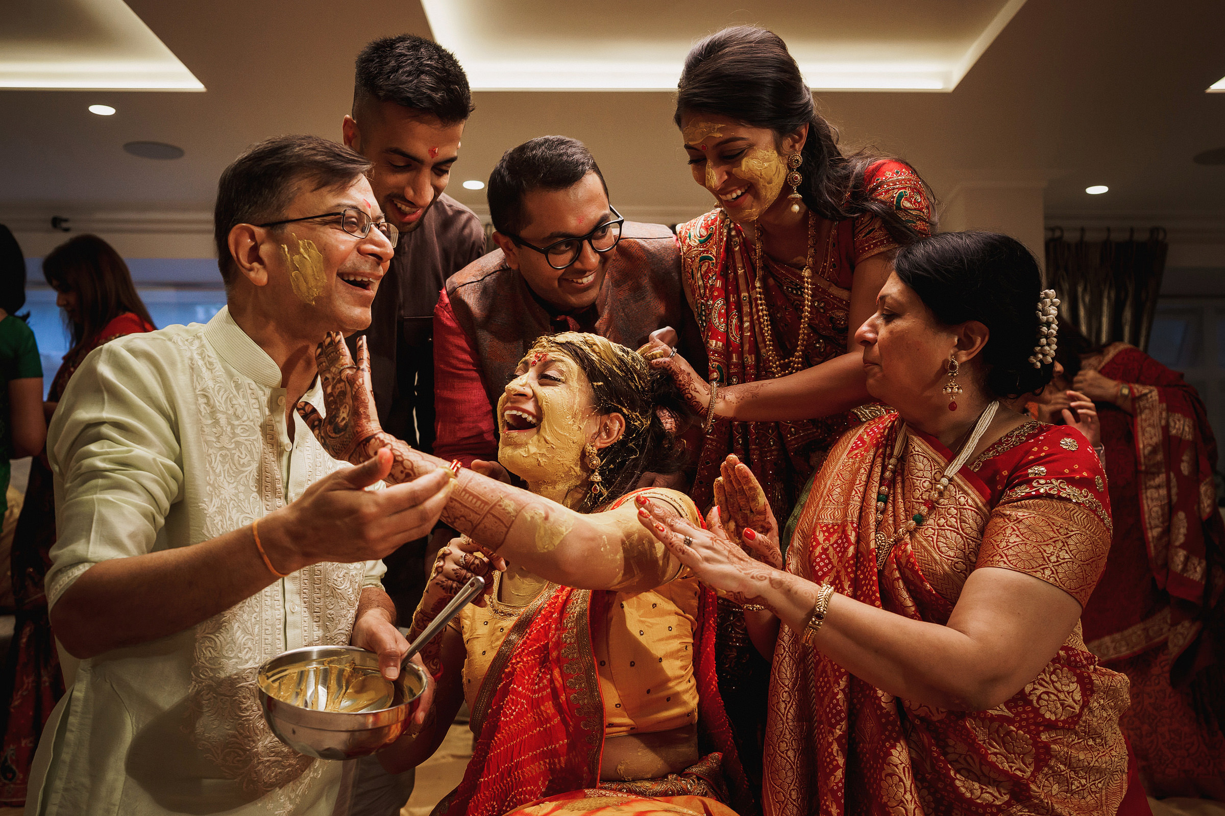 Joyful photo of Indian family during saffron wedding ceremony by f5 best London wedding photographr