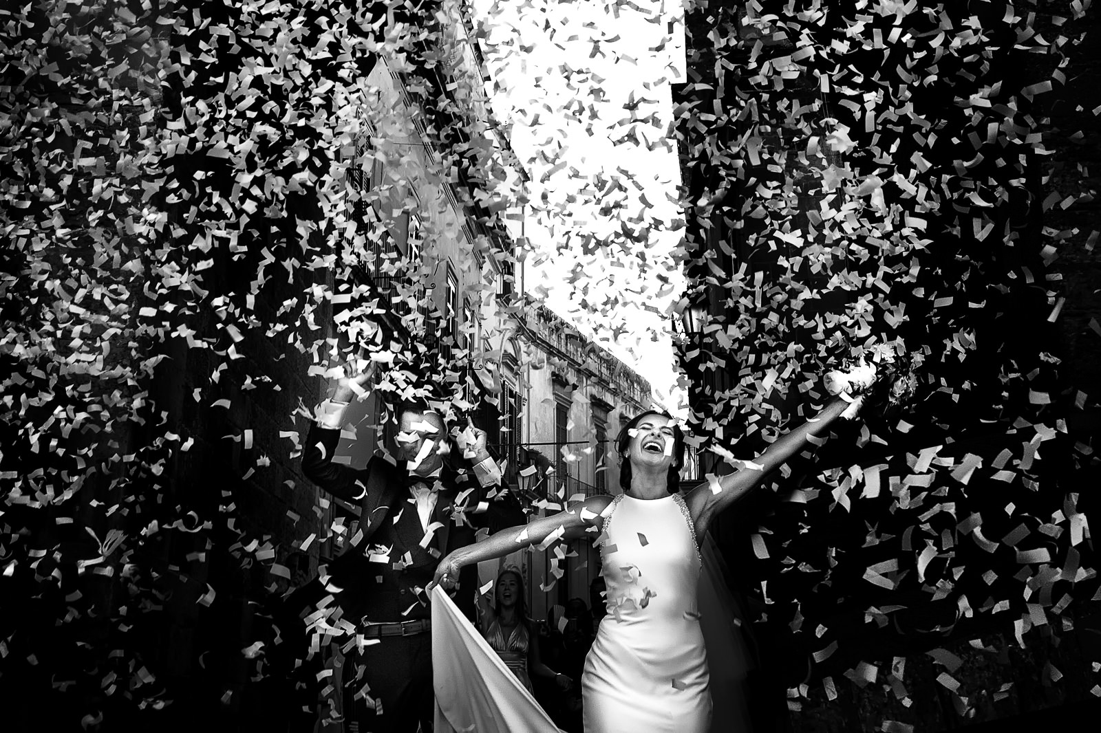 just-married-couple-under-shower-of-confetti-photo-by-rino-cordella-wedding-photographer-lecce-italy
