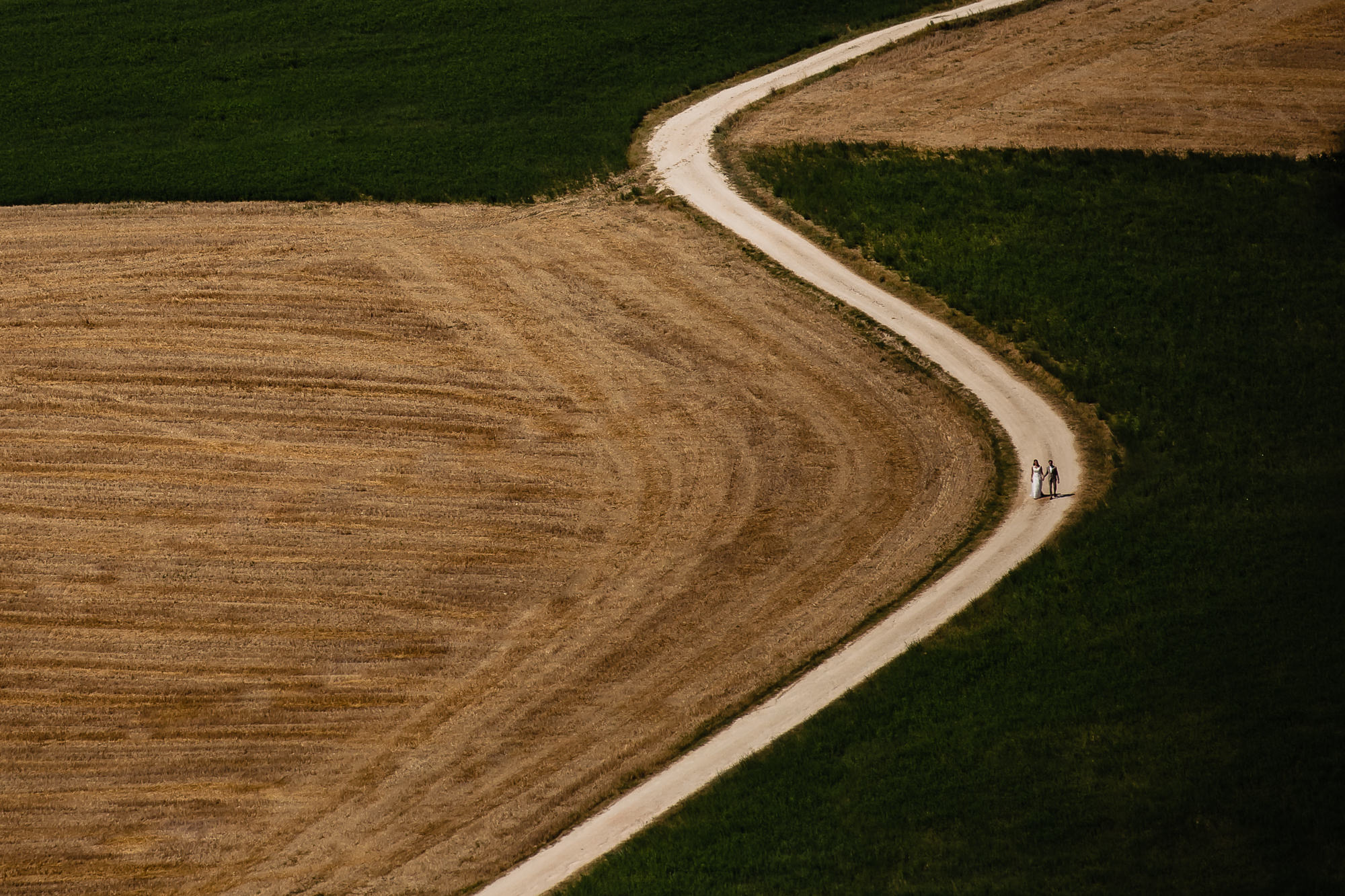 Couple on long winding path through field - photo by Eppel Photography - Netherlands