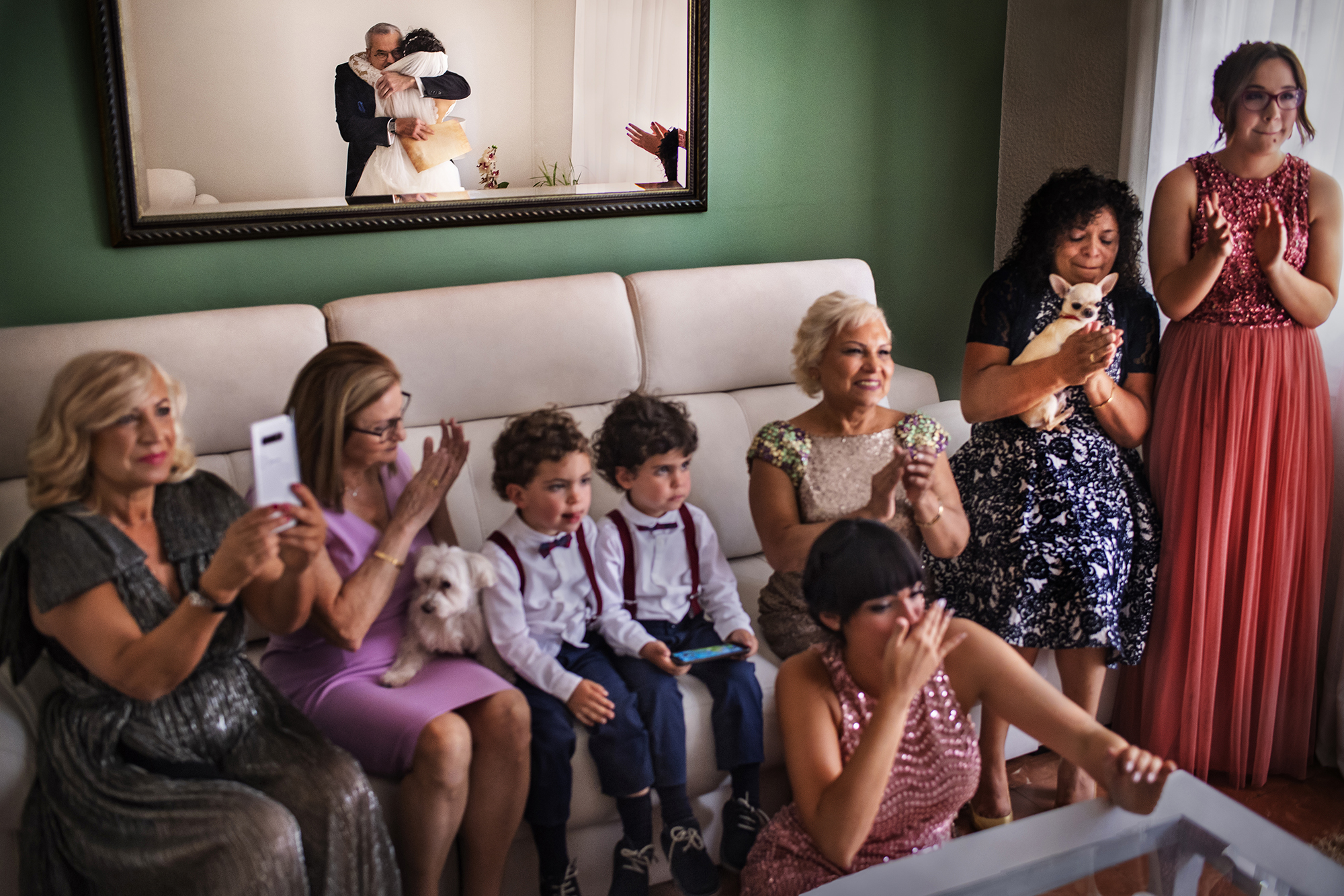 Reflection of father and bride embracing in room full of family member - photographed by Victor Lax - Spain