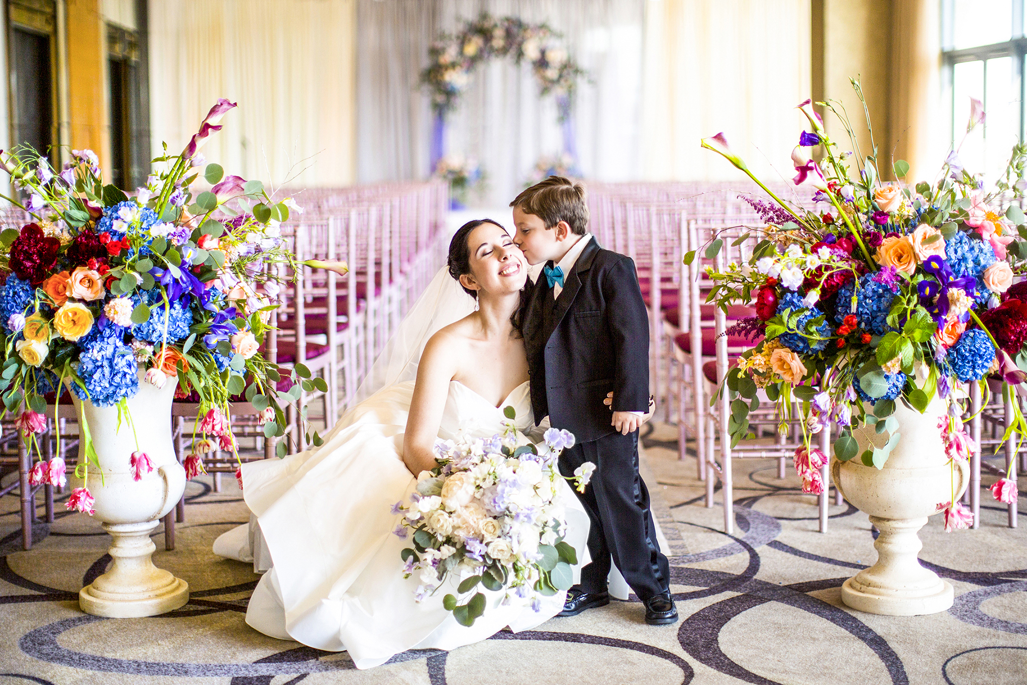 Boy wearing black tux and bright blue bowtie kisses bride in aisle - photo by Anna Schmidt
