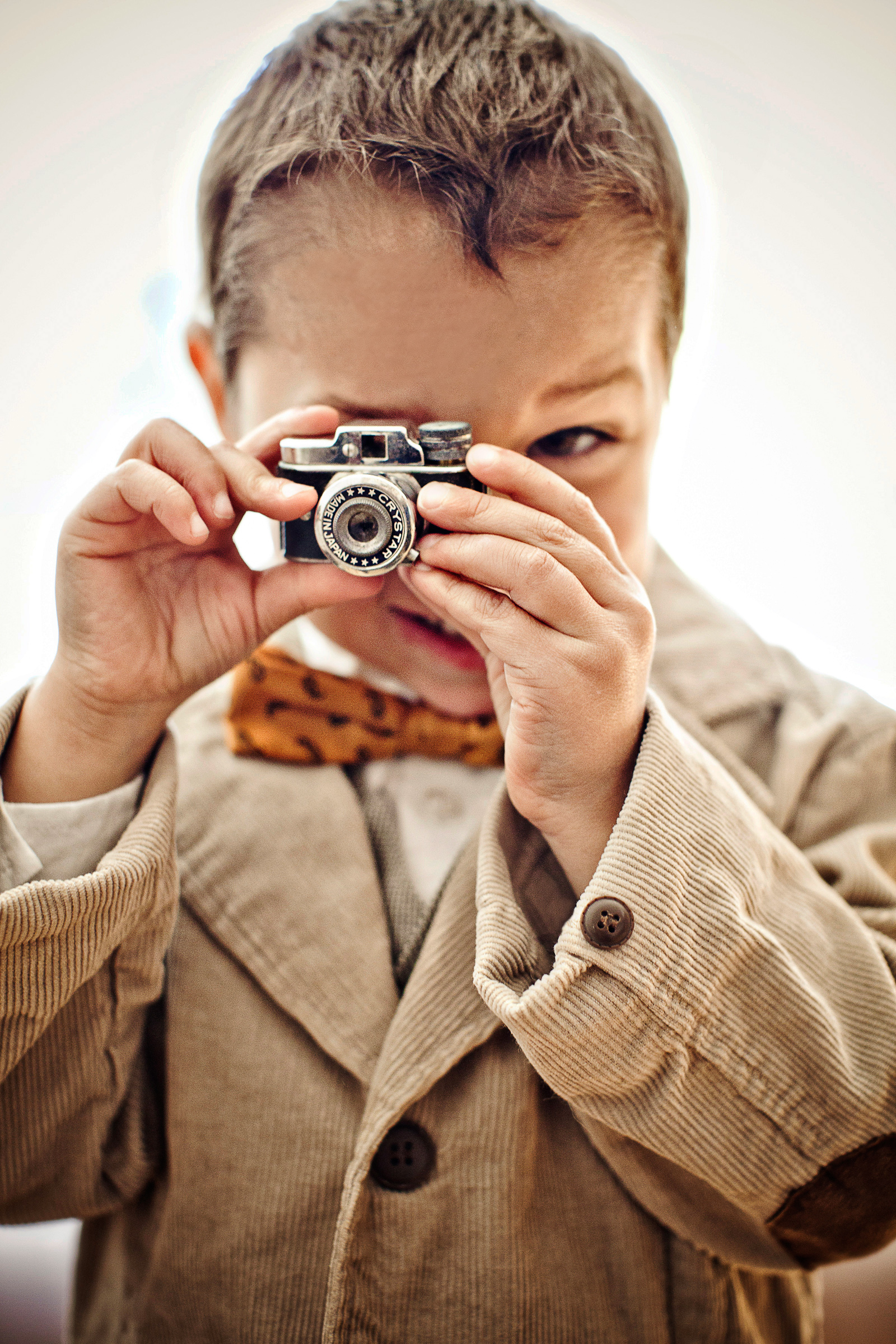 Little boy with brown corduroy coat and toy camera - photo by Jag Studios