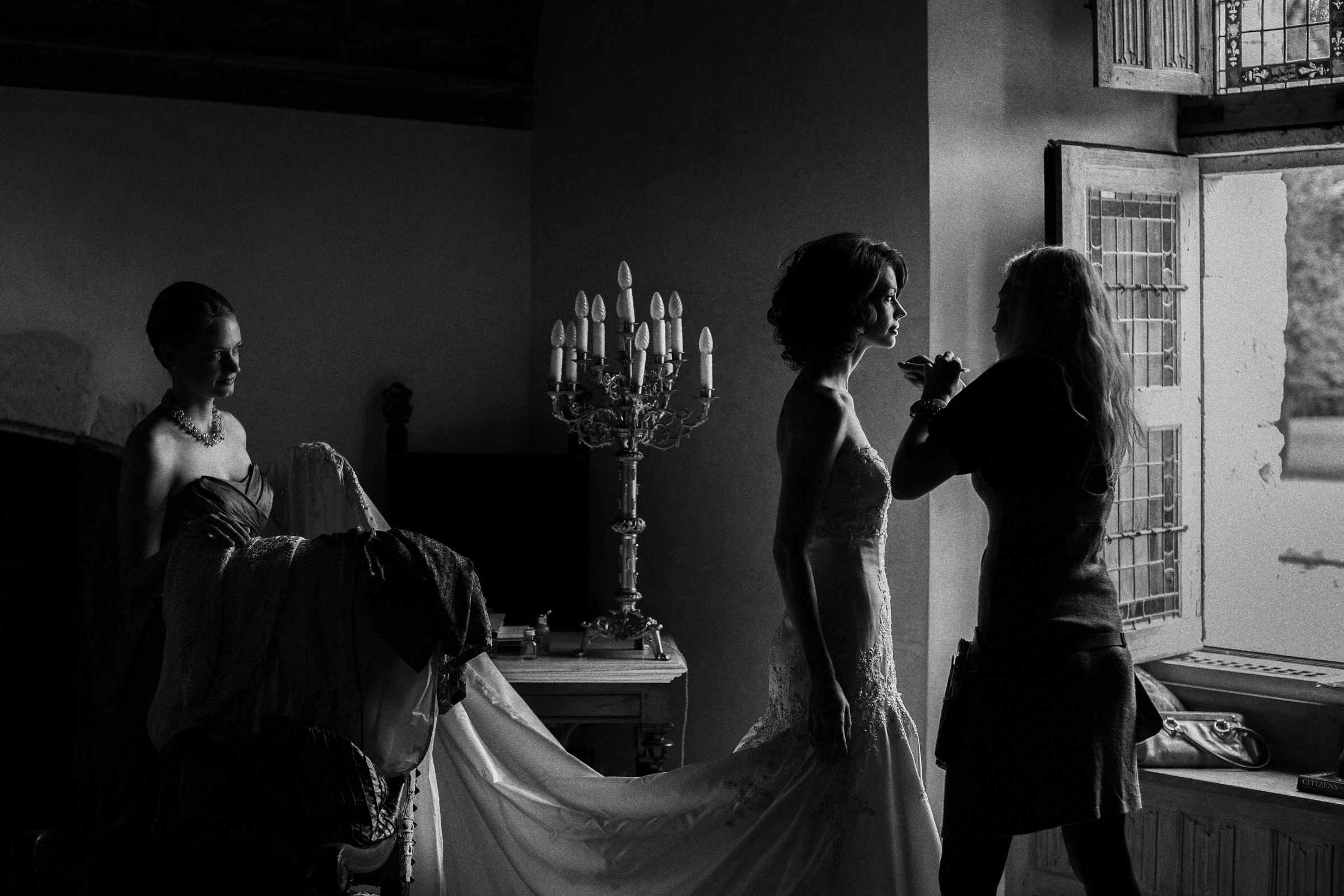 Make-up artist puts final touches on bride in windowlight - photo by Jeff Ascough - England