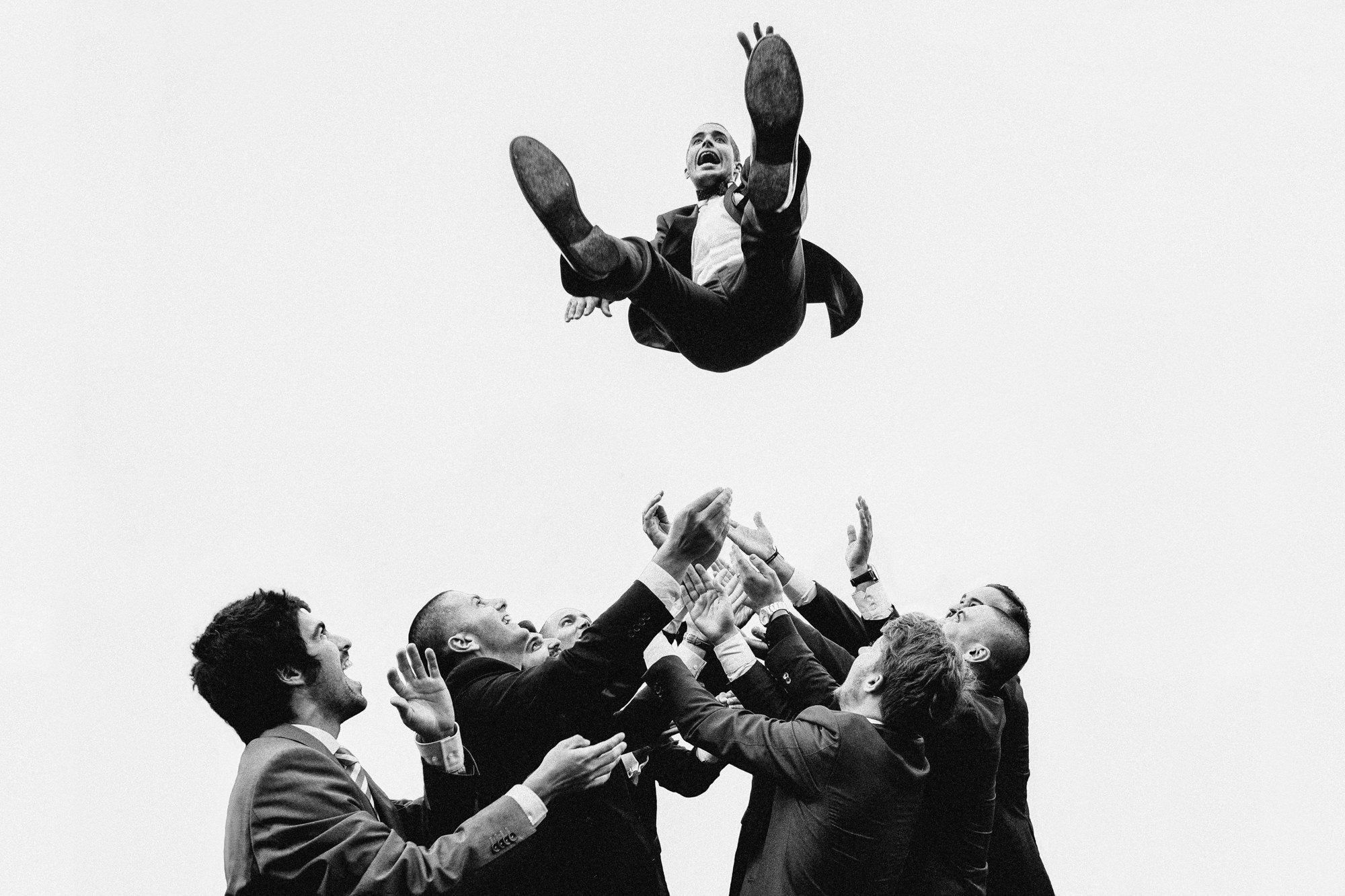 Groom tossed way in the air by groomsmen