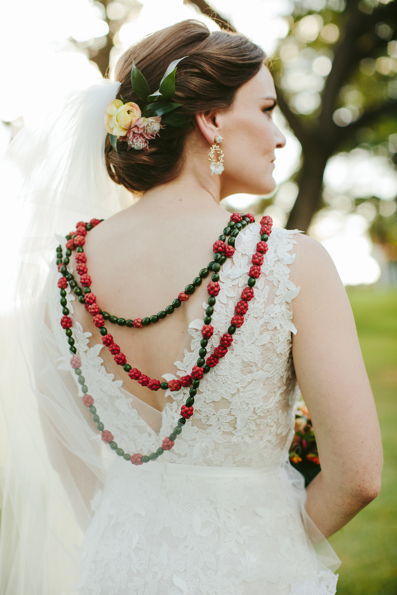 Bride with red and green Hawaiian jewelry photographed by Melia Lucida - Maui
