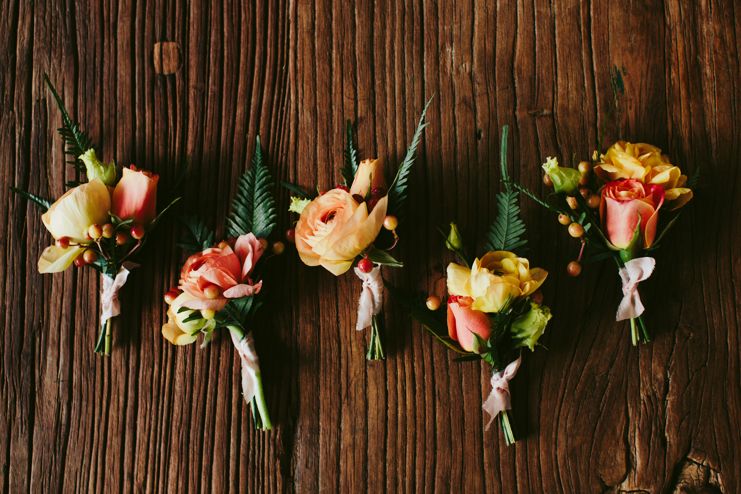 Yellow and coral rose and fern boutonnieres - photo by Melia Lucida - Maui wedding photographer