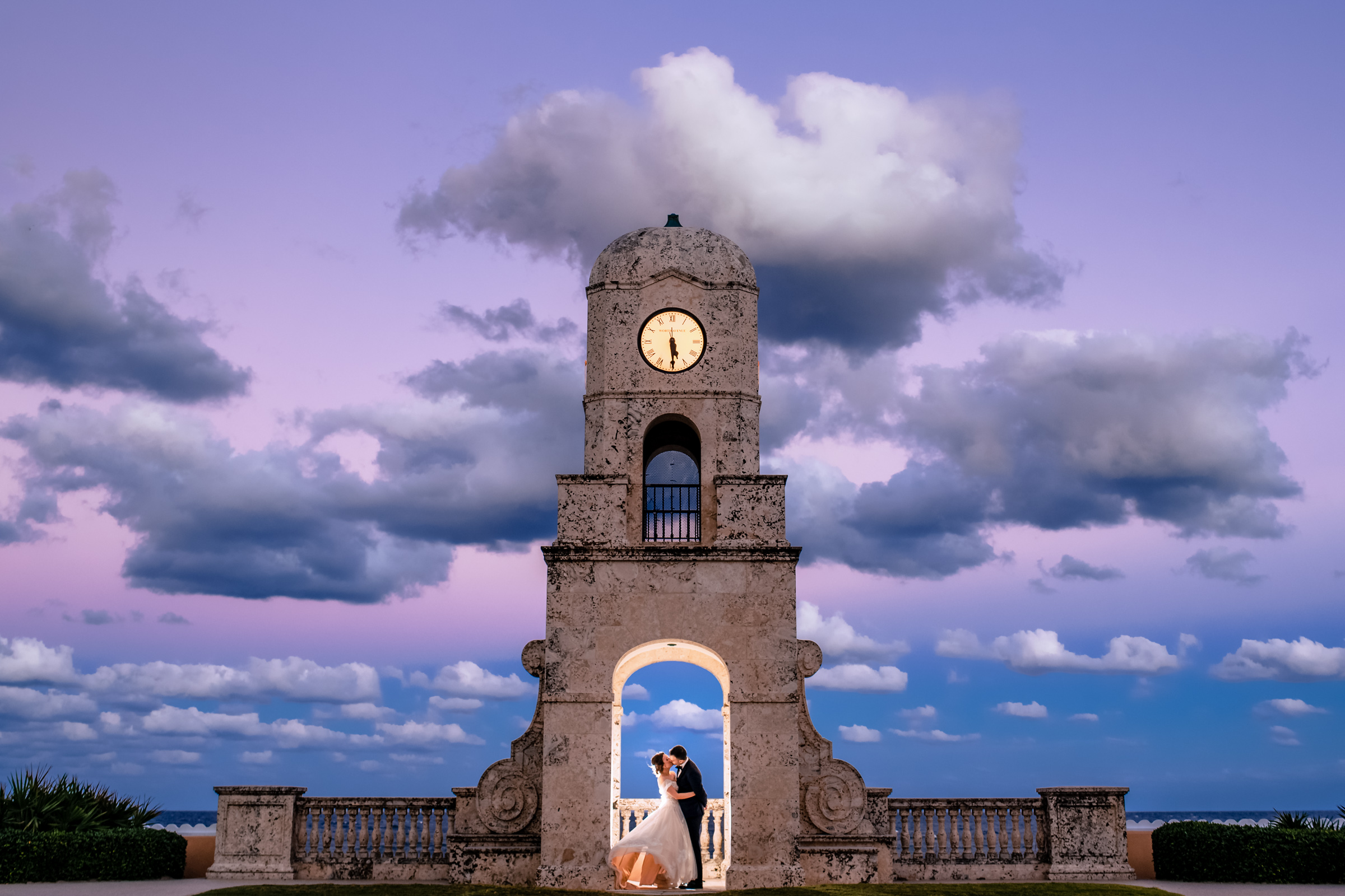 portrait-of-bride-and-groom-kissing-under-clock-tower-during-pink-sunset-michael-freas-photography-north-carolina