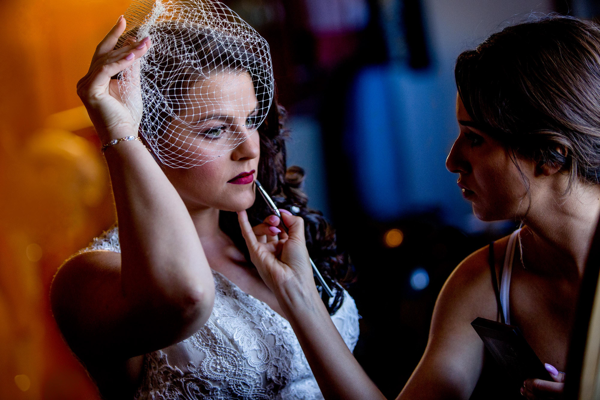 Make-up artist applying red lips to bride in birdcage veil - photo by Jos & Tree - Portland