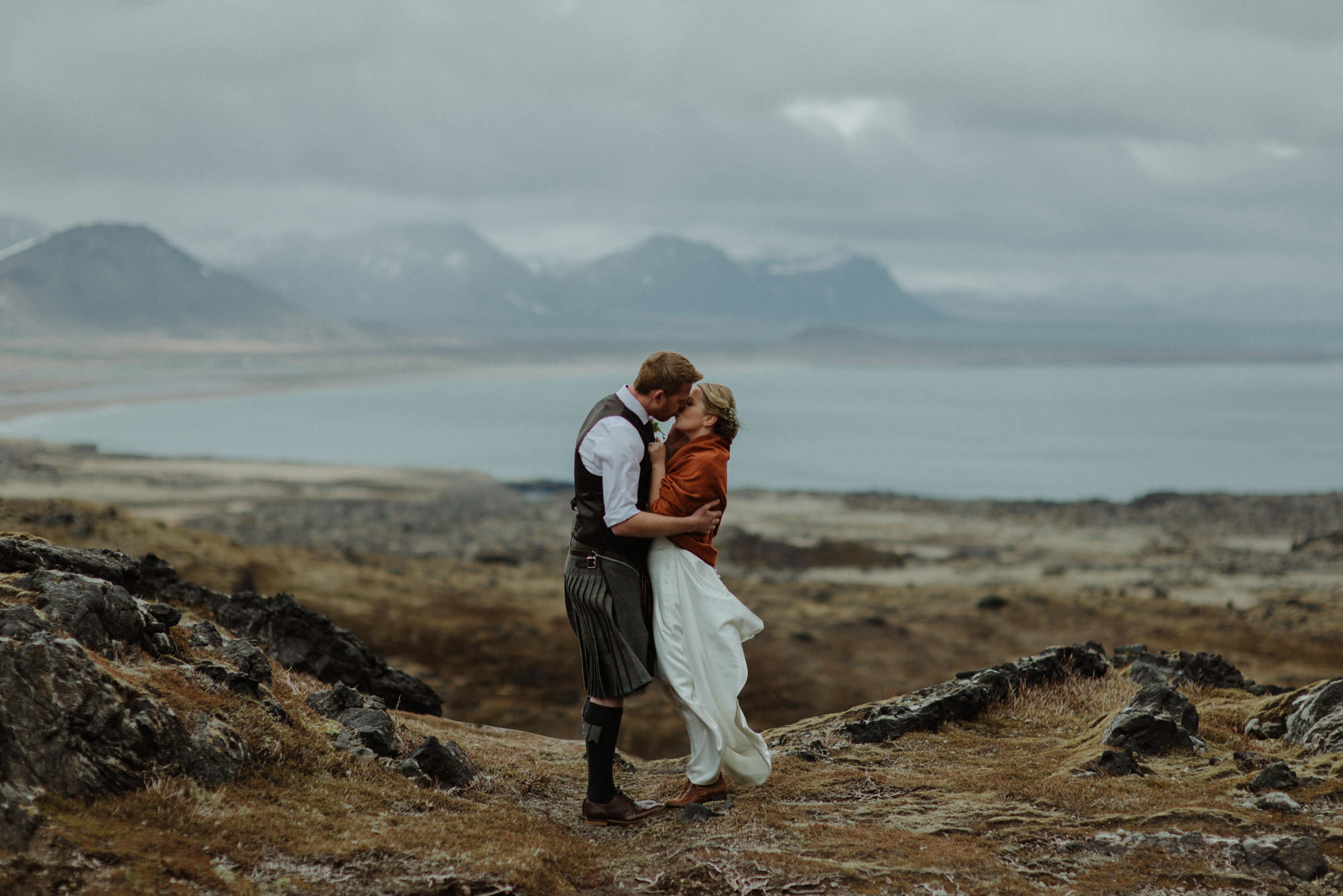 Groom in kilt kissing bride against Scottish landscape - photo by The Kitcheners
