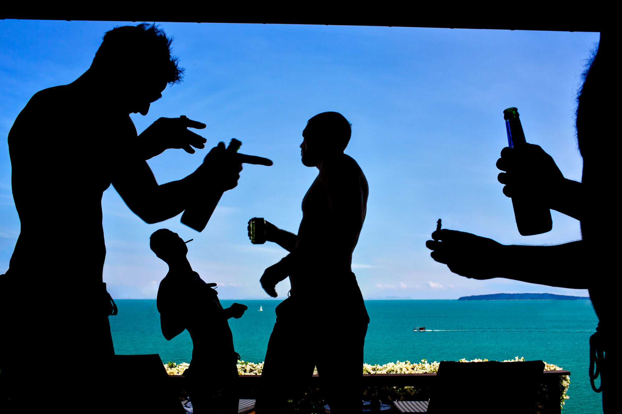 Silhouette of guys celebrating at beach wedding - photo by Two Mann Studios