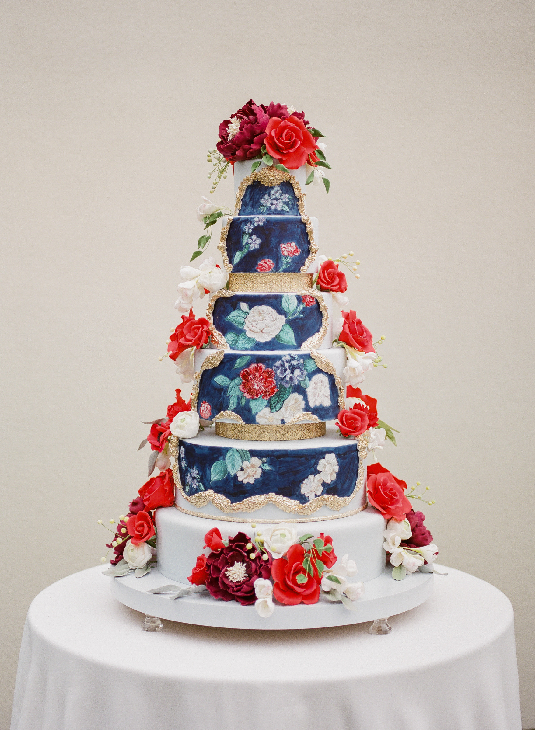 six-tiered-floral-painted-wedding-cake-blue-with-red-roses-photographed-by-corbin-gurkin-worlds-best-wedding-photos
