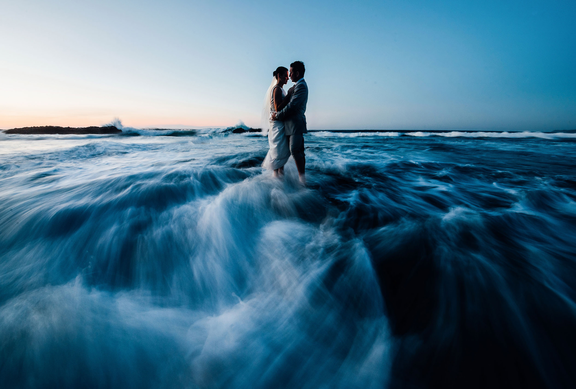 Slow exposure of couple standing in ocean waves - photo by The Brenizers
