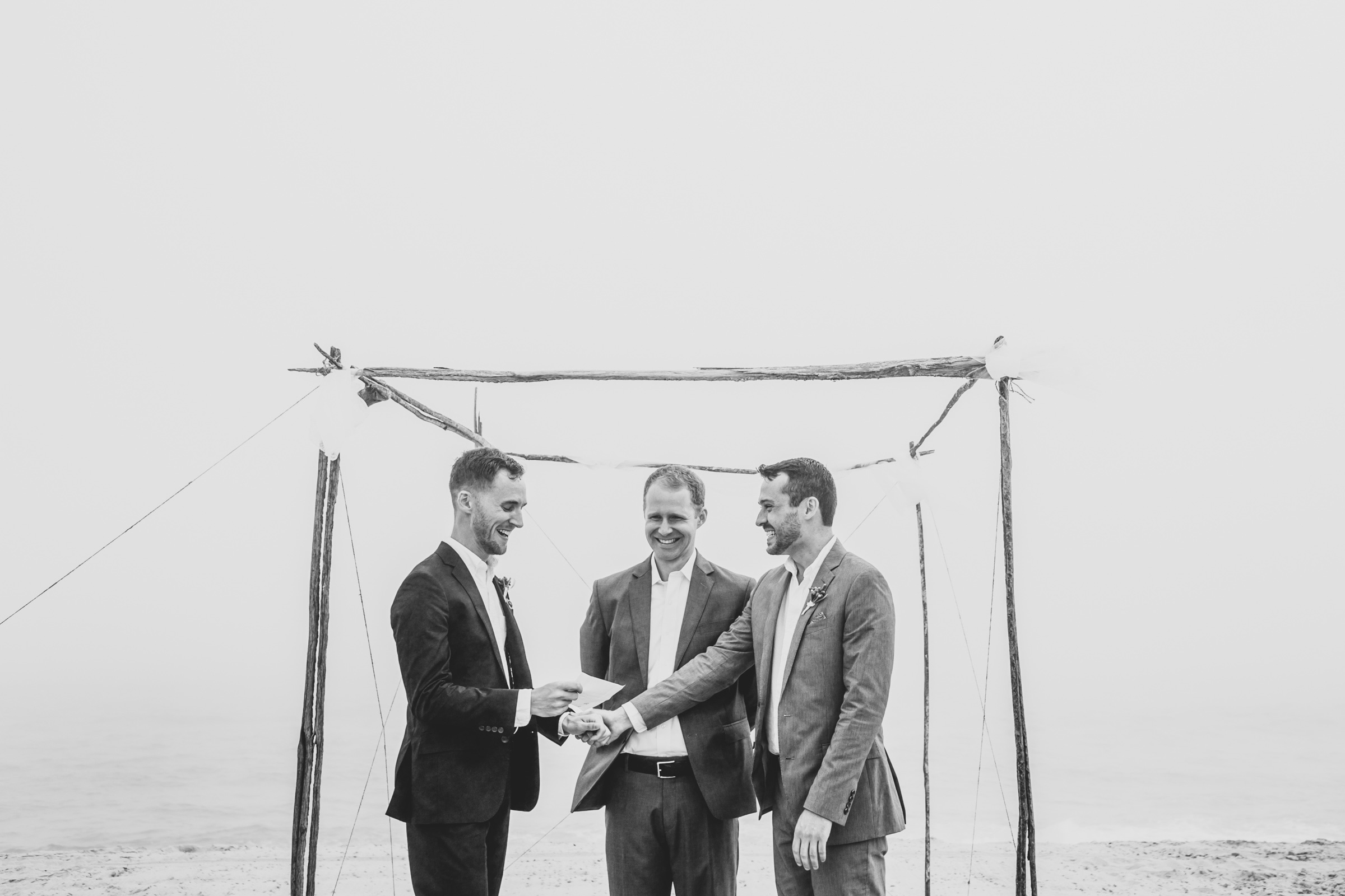two-grooms-at-ceremony-under-natural-arbor-katie-kaizer-photography