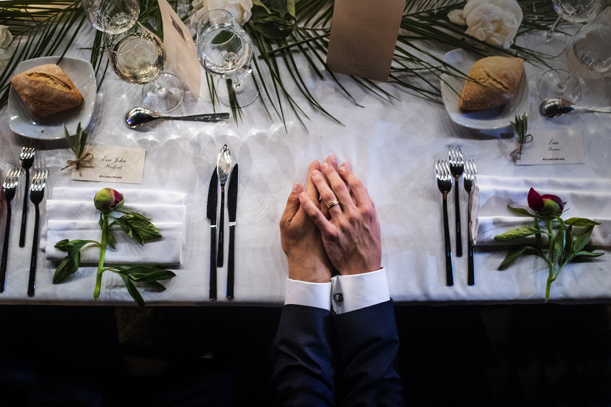 2 grooms holding hands at dinner - photo by Victor Lax - Spain