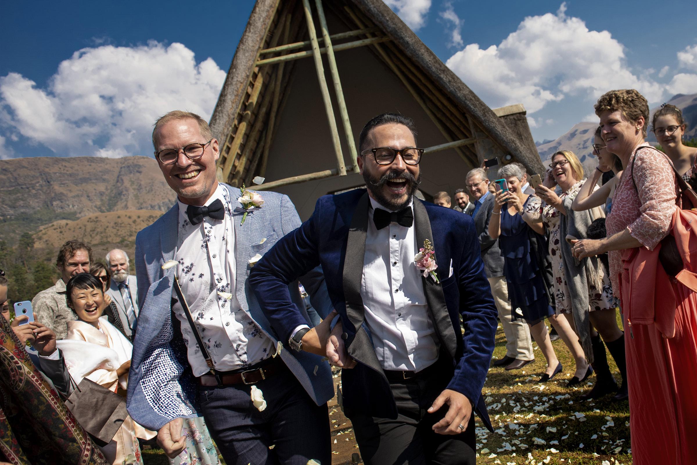 two-joyful-grooms-exit-their-ceremony-jacki-bruniquel