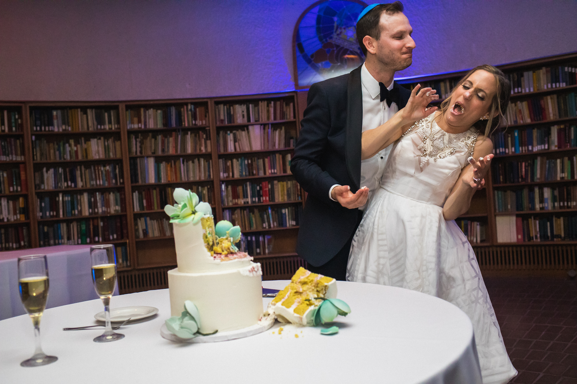 Bride gets a face full of wedding cake from groom - photo by Annie Bang - California