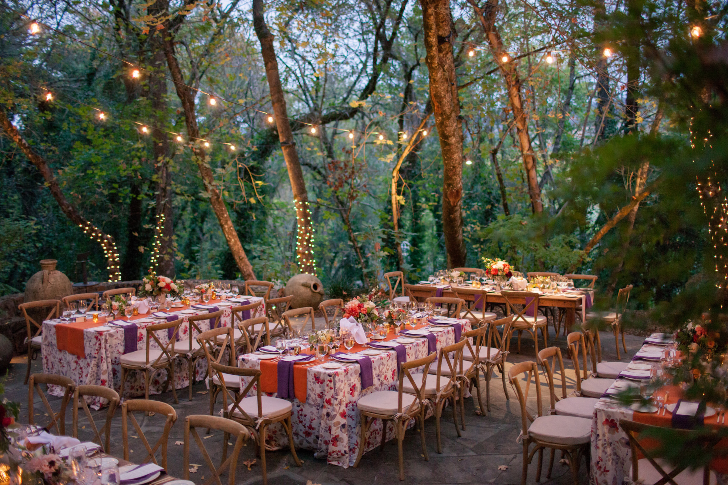 Woodland lighted reception with floral tablecloths photographed by Modernmade Weddings - Florida