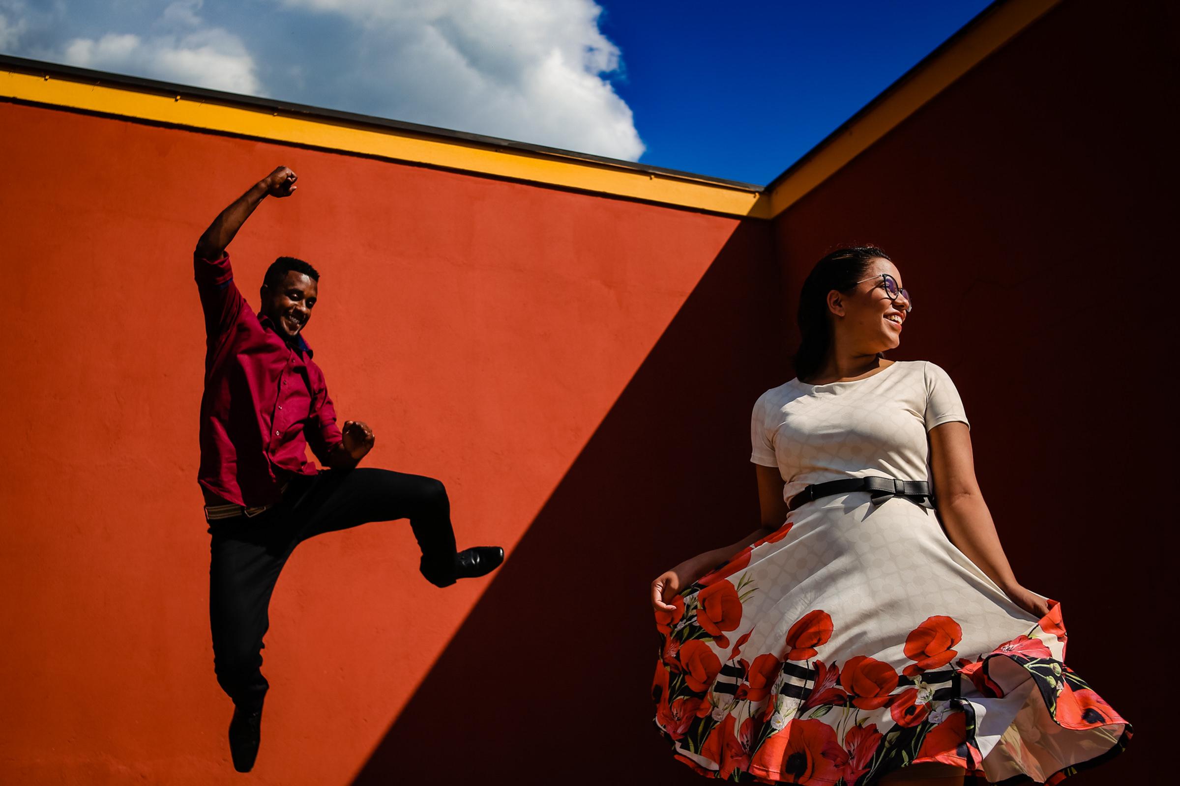 Groom jumps with joy while bride swirls her dress - Award-winning photo by Area da Fotografia - Brazil