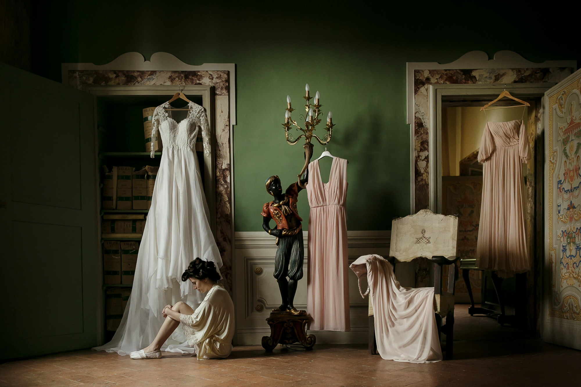 Bride sits on the floor in front of her wedding gowns - photo by David Bastianoni - Italy