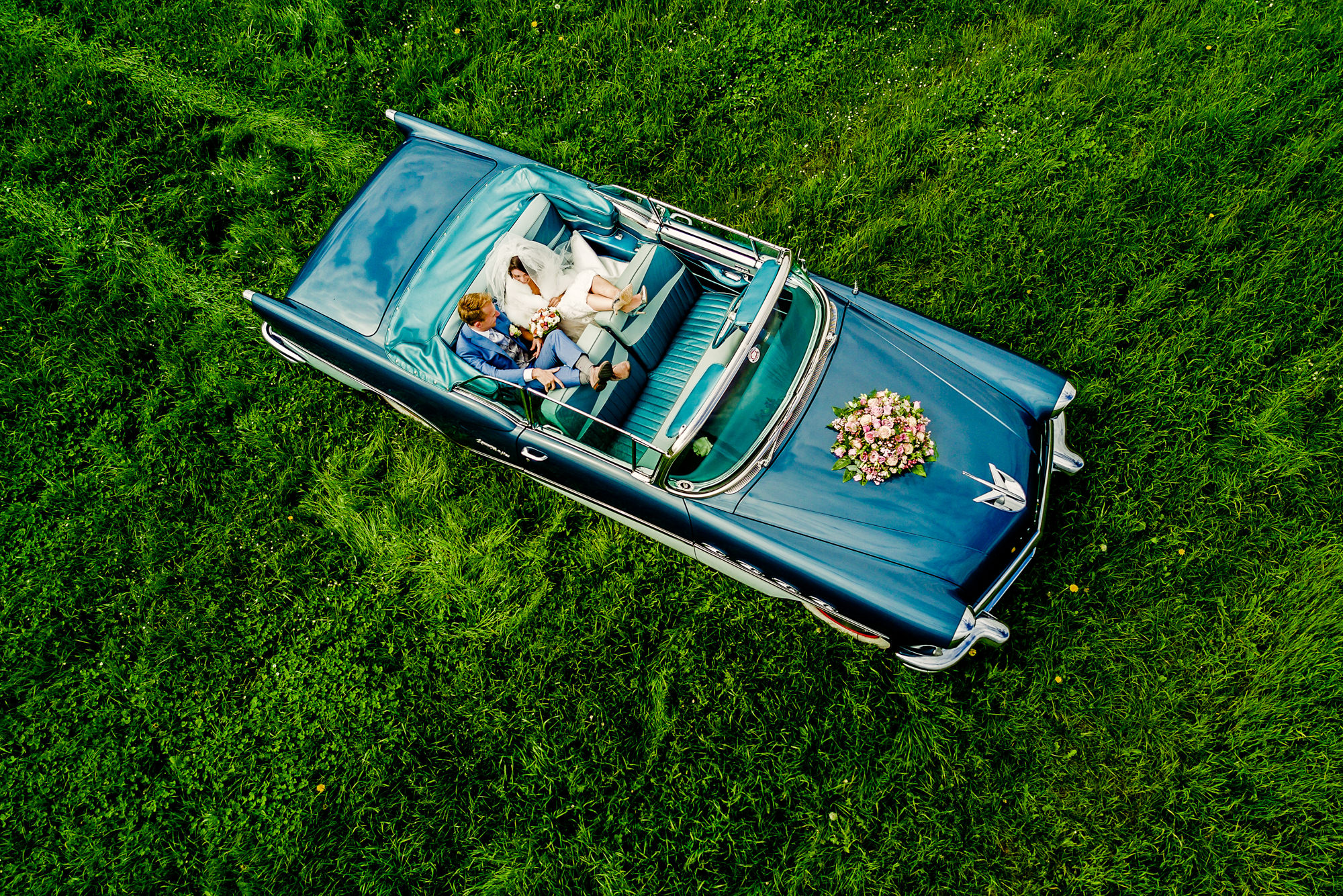 Bride and groom make their getaway in teal convertible Cadillac Deville - drone photo by Eppel Photography