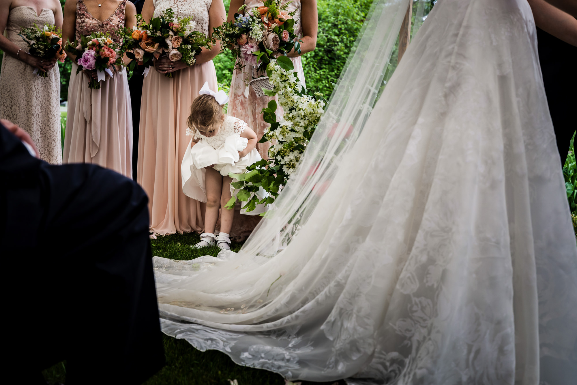 Flower girl looking at her shoes during ceremony - photo by JAG Studios