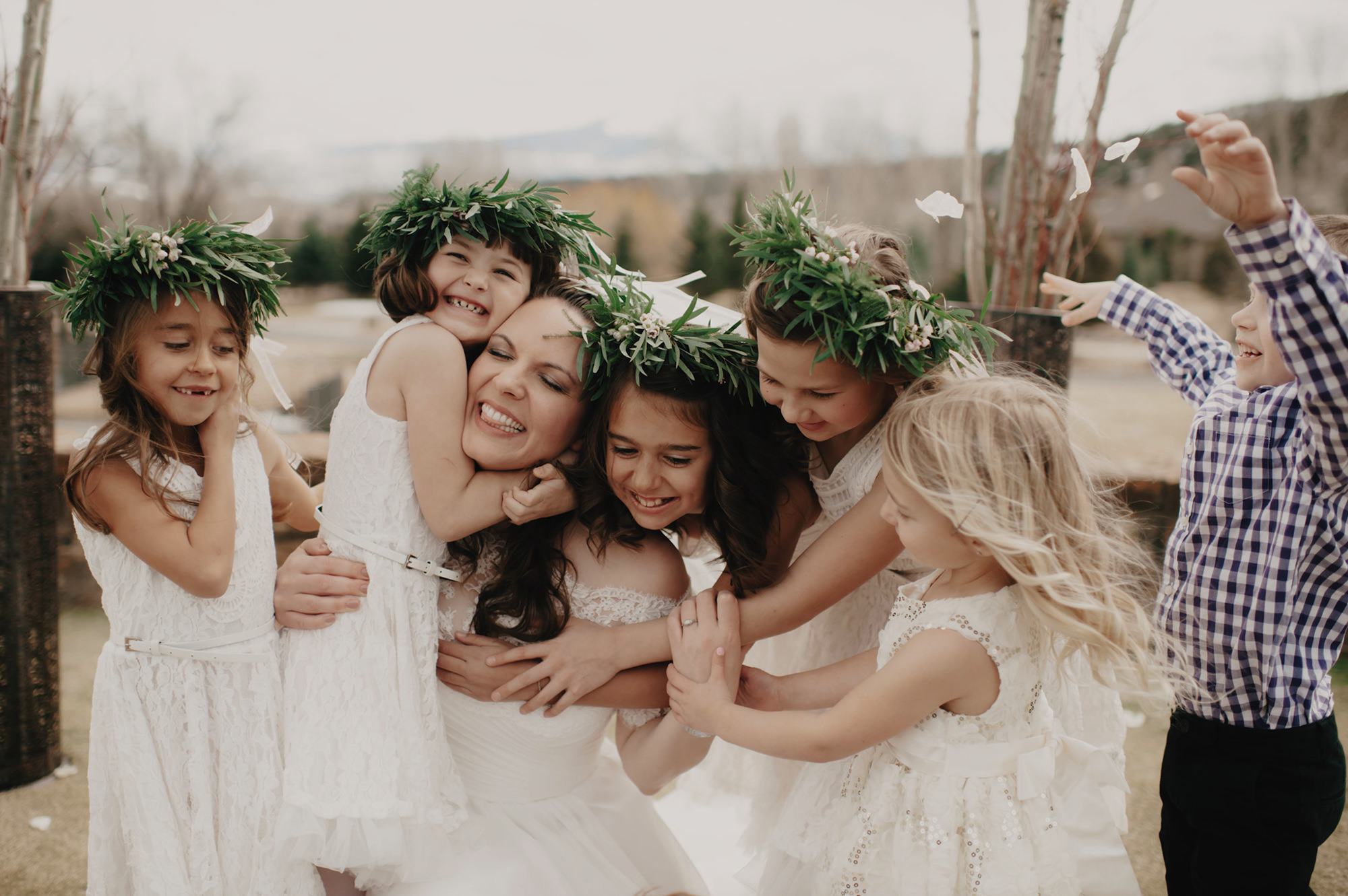 Adorable little girls with tropical grass head pieces hugging bride - photo by Kristen Marie Parker