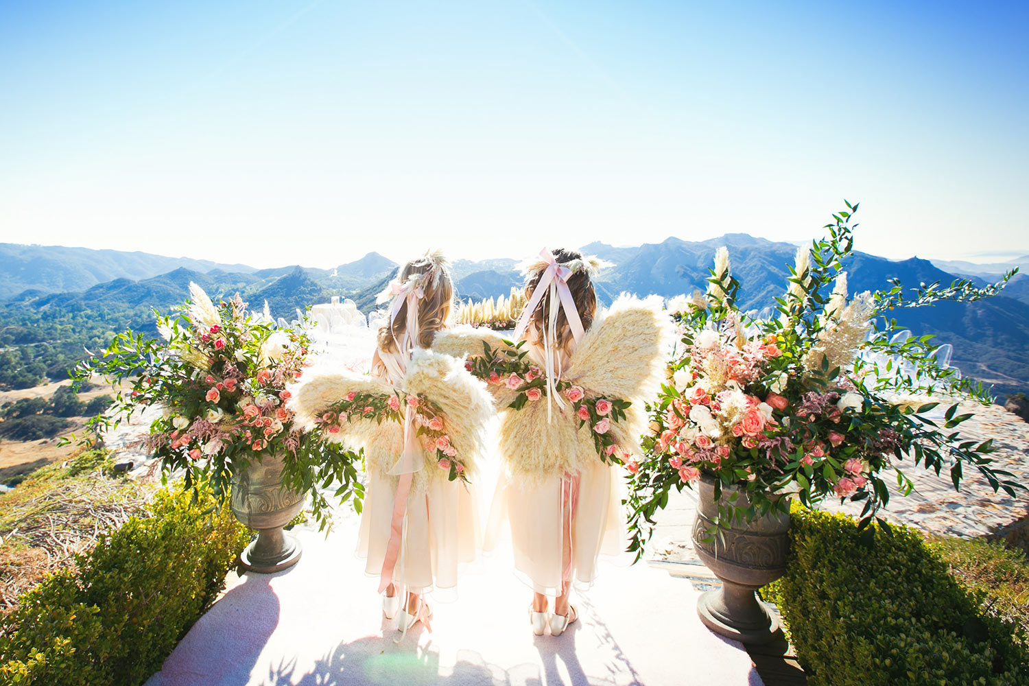Flower girls in angel wings against mountains, by Callaway Gable
