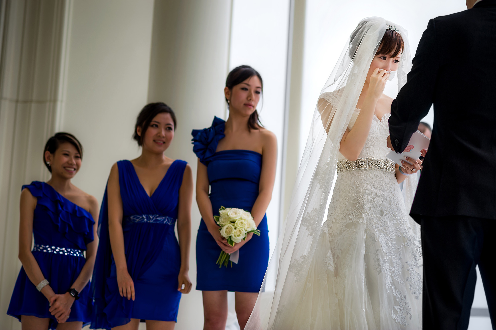 Bride in lace gown and veil wiping away ears with bridesmaids - Davina + Daniel