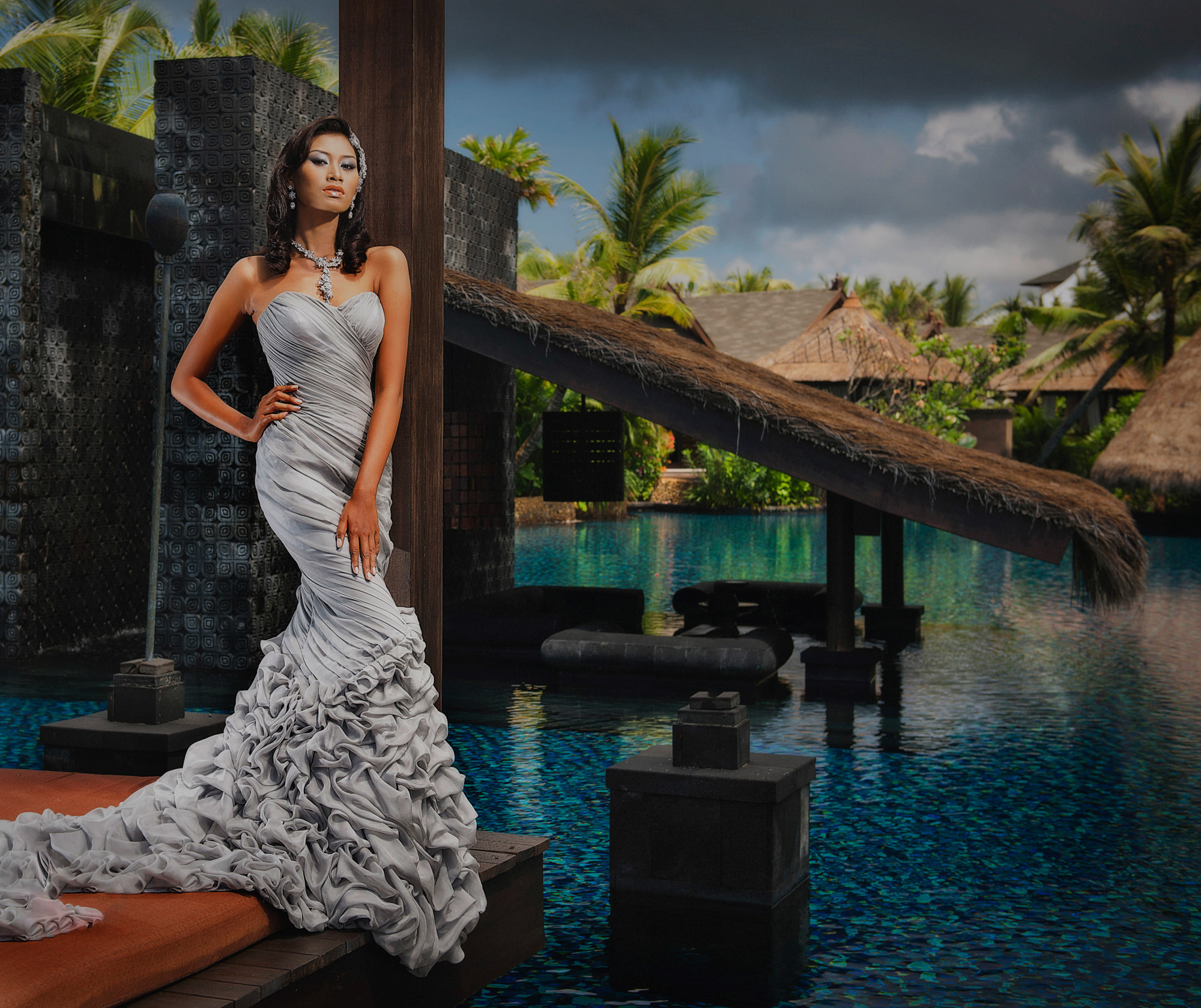 Fashionable Asian  bride standing by luxury resort lagoon  - Studio Impressions Photography