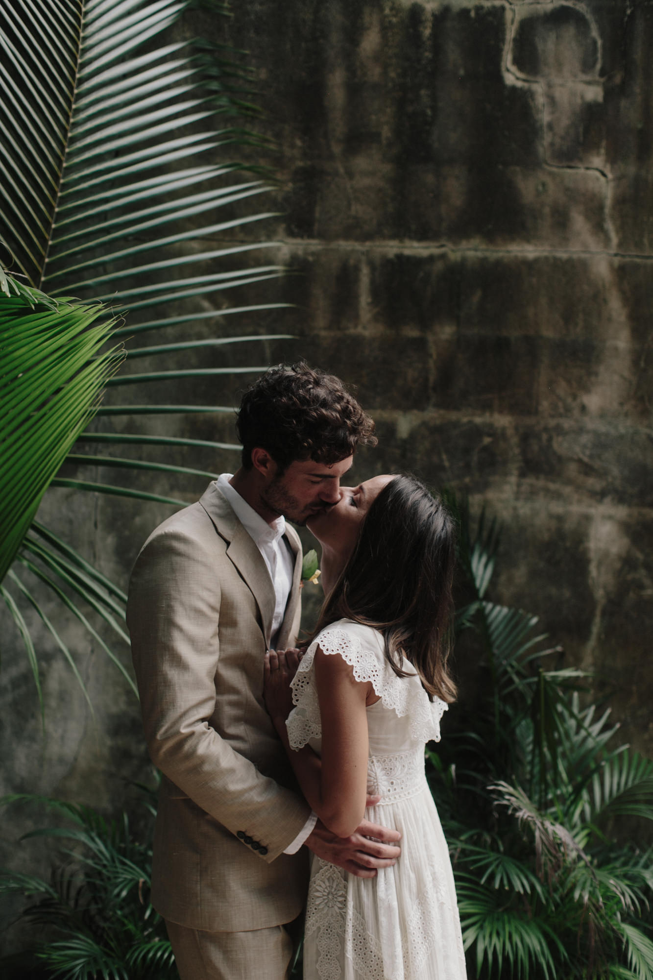 Couple kissing under palm frond - photo by James Moes