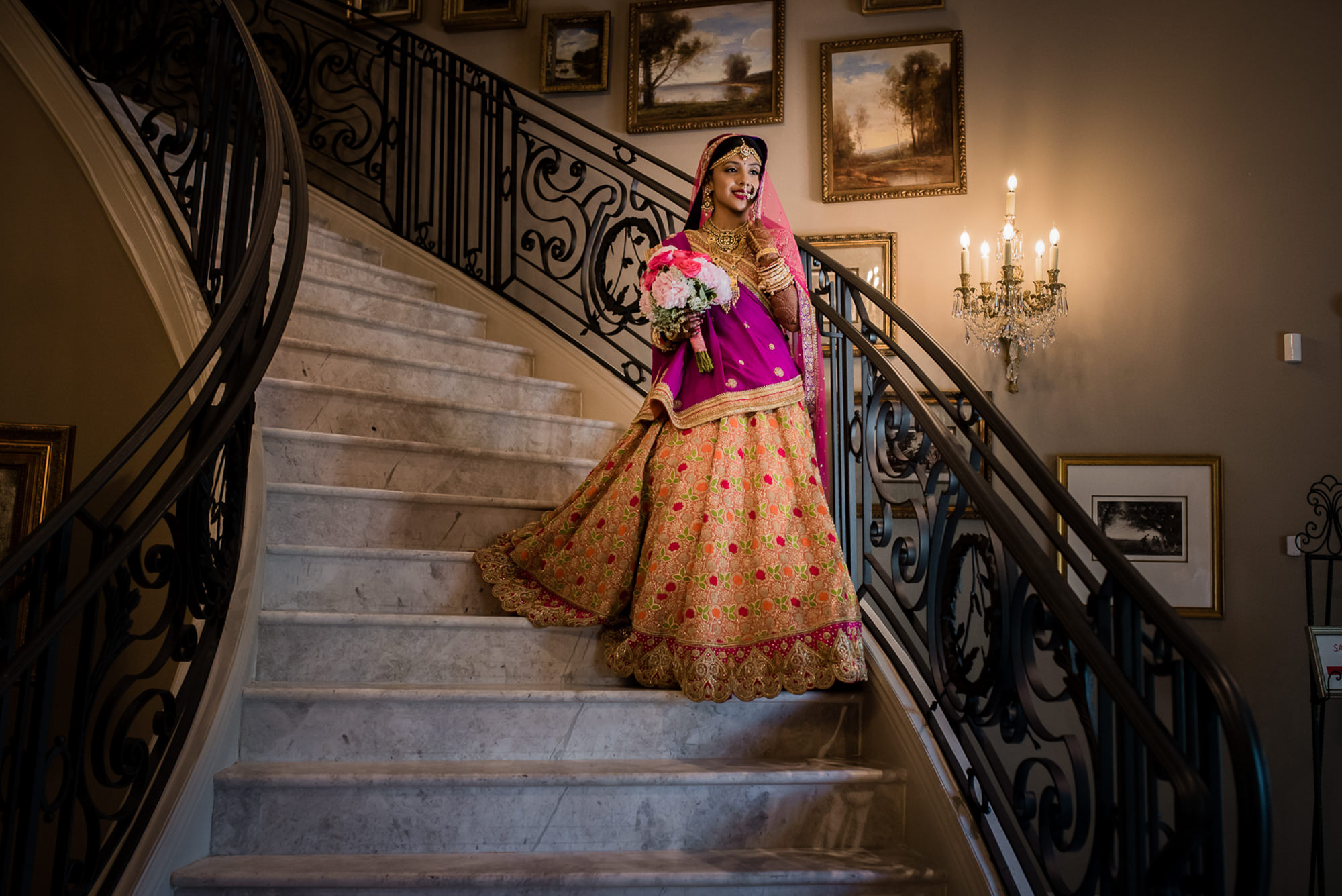 Beautiful Indian bride on staircase in Fuschia and Gold by Rimi Sen
