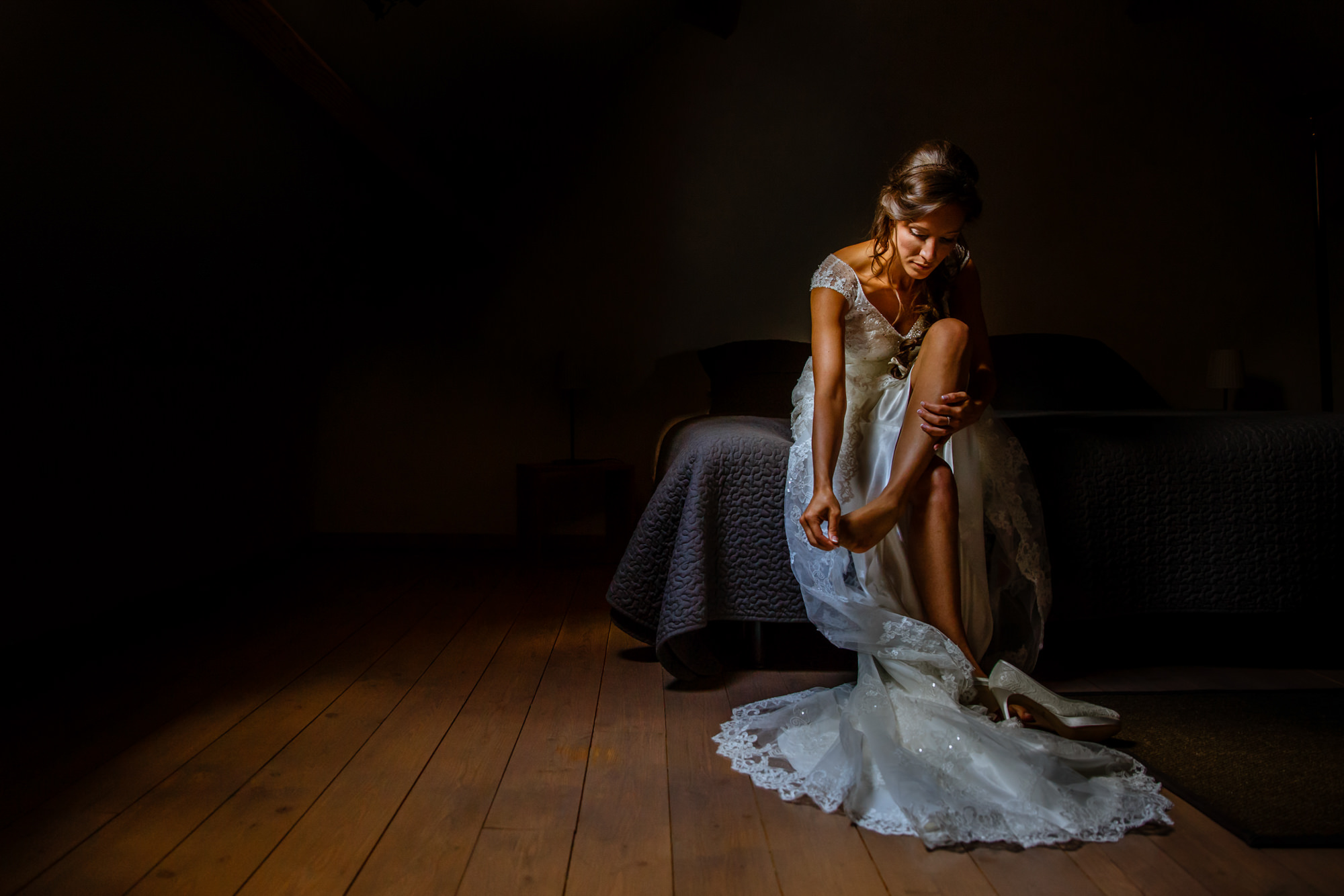 Bride putting on her shoes in low light - photo by Philippe Swiggers