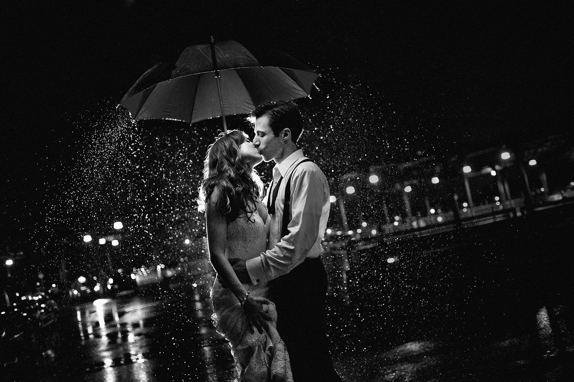 Nighttime couple kiss under umbrella -  Davina + Daniel