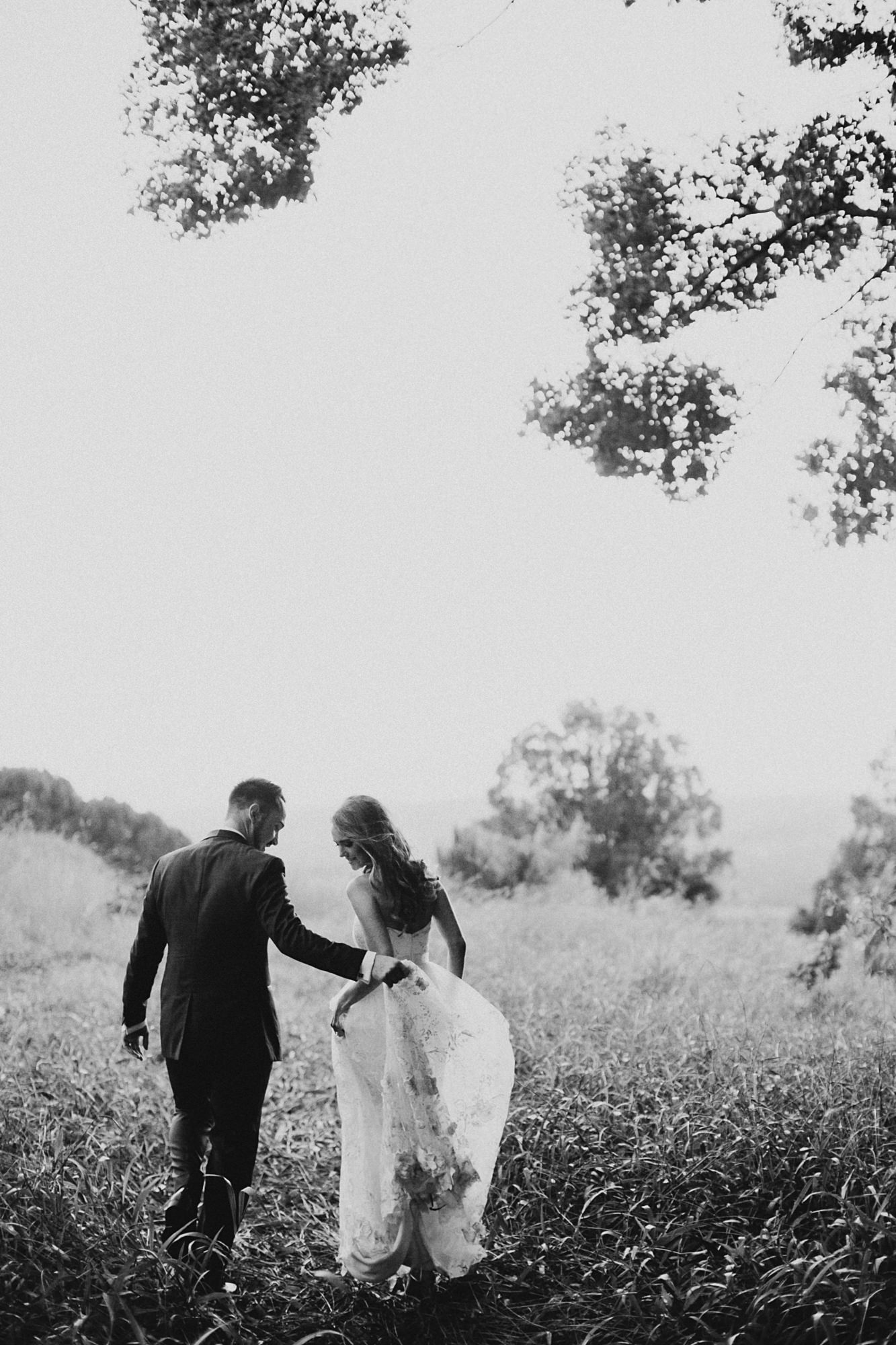 Bride and groom walking through field- photo by Dan O'Day