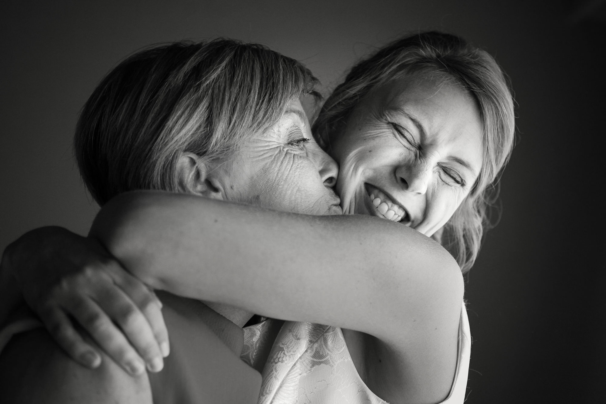 Happy bride hugging her mother - photo by Philippe Swiggers