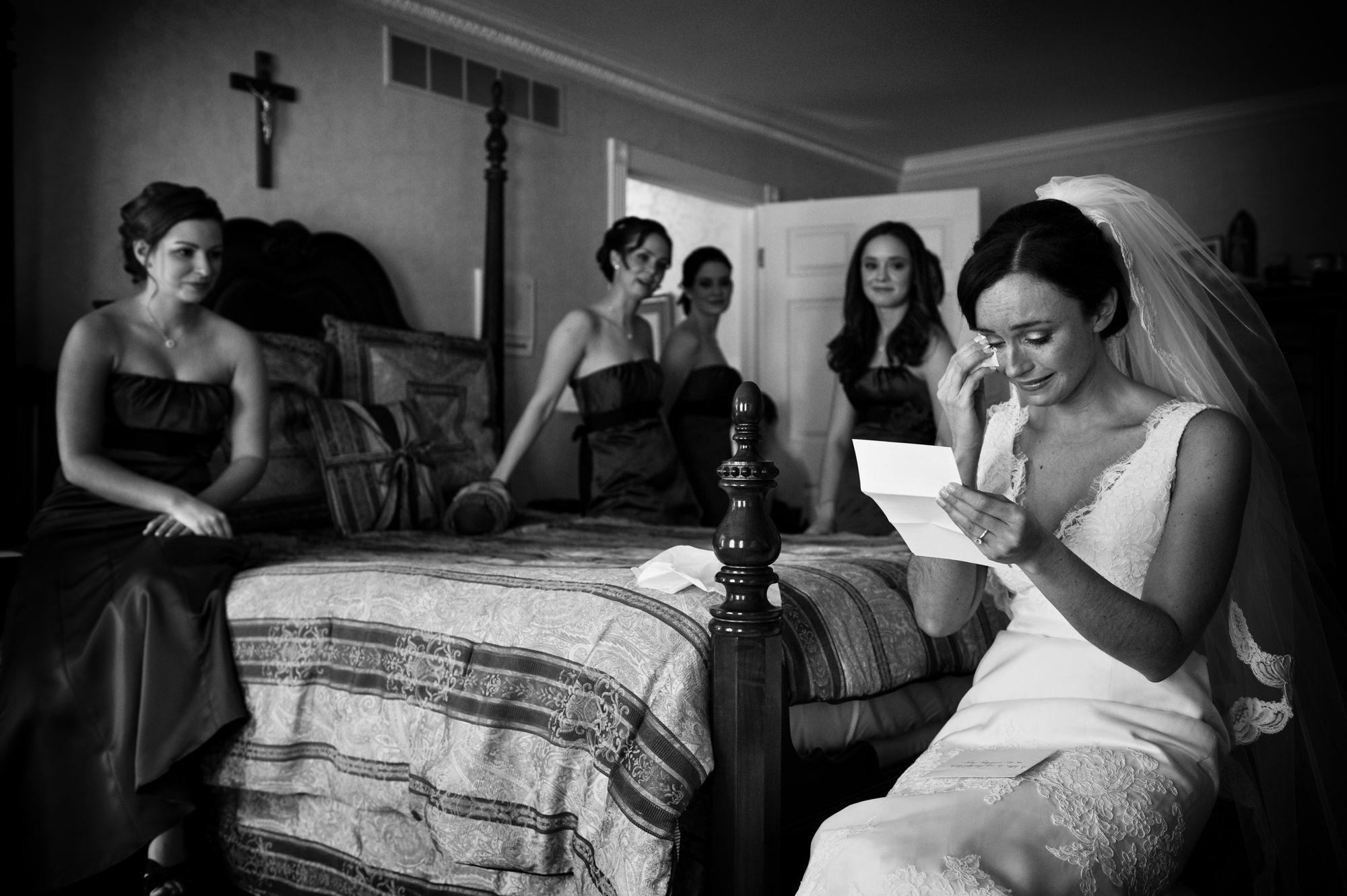 Bride tearing up reading letter from groom with bridesmaids watching, by Cliff Mautner
