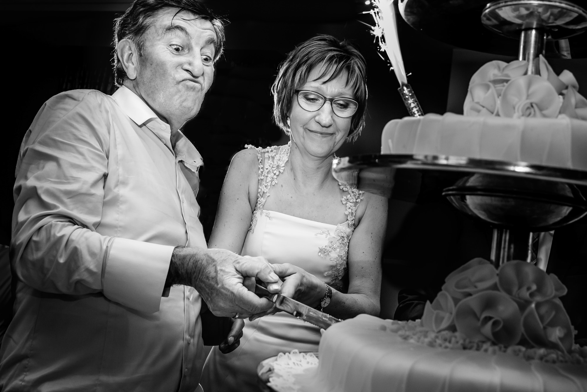 Fun bride and groom cutting wediding cake - photo by Philippe Swiggers