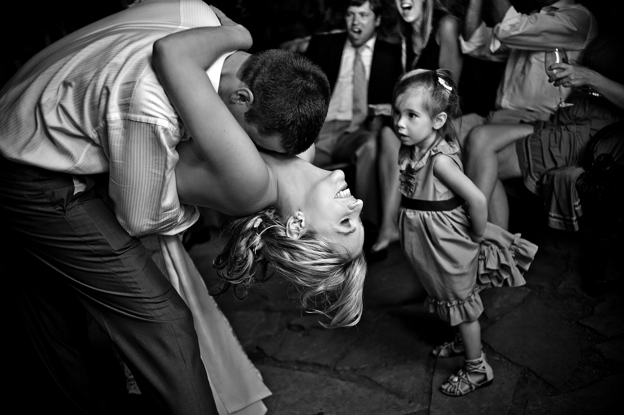 Groom dips bride while little girl watches - Davina + Daniel