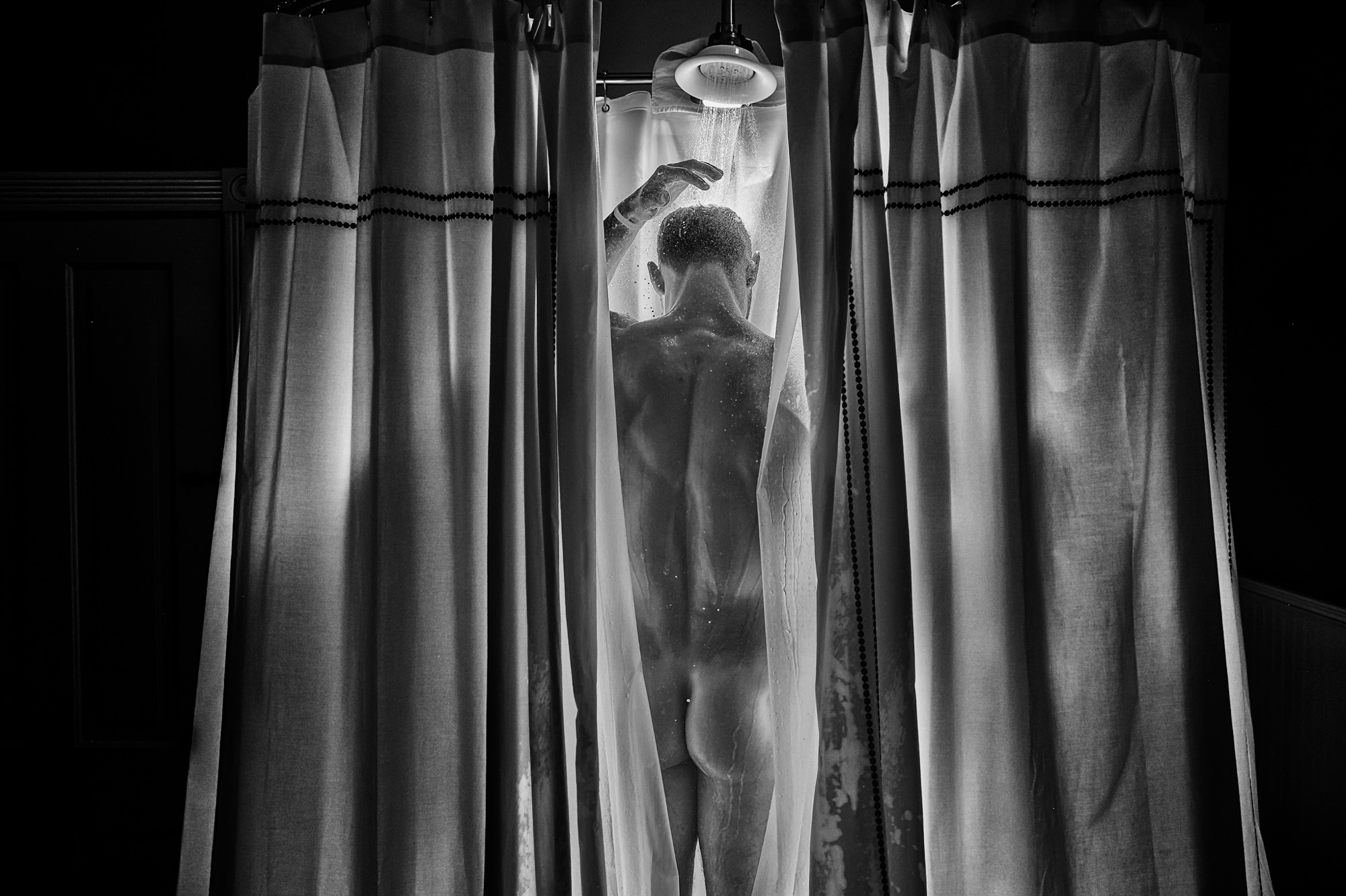 Groom showering framed by shower curtains, by Chrisman Studios