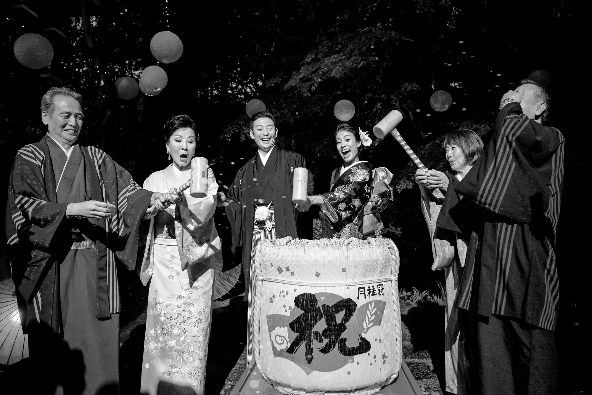 Fun black and white photo of Japanese couple hitting mochi with mallets with parents, by 37 Frames
