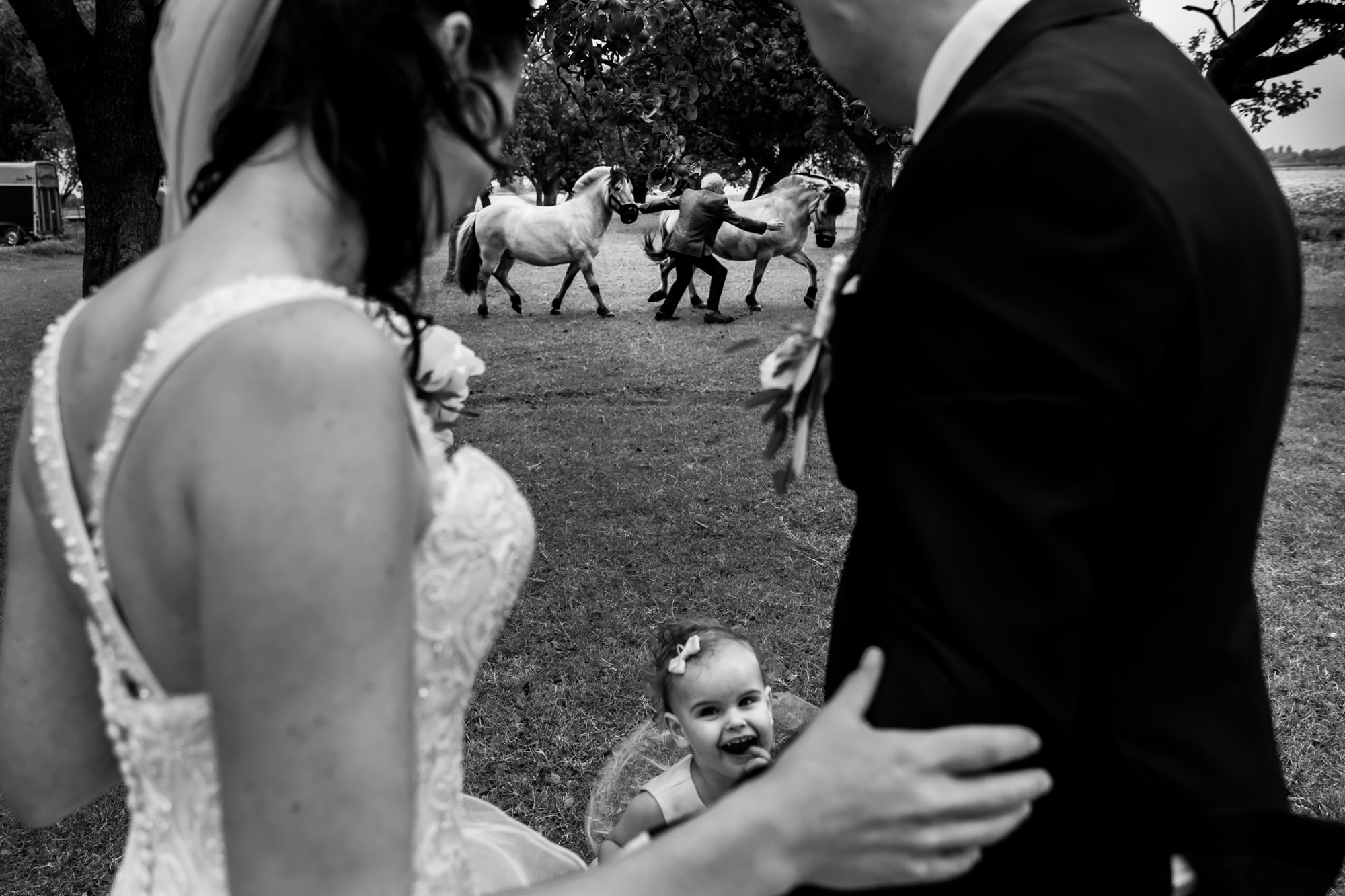 Child framed by couple with horses in the background photo by Fotobelle: Isabelle Hattink