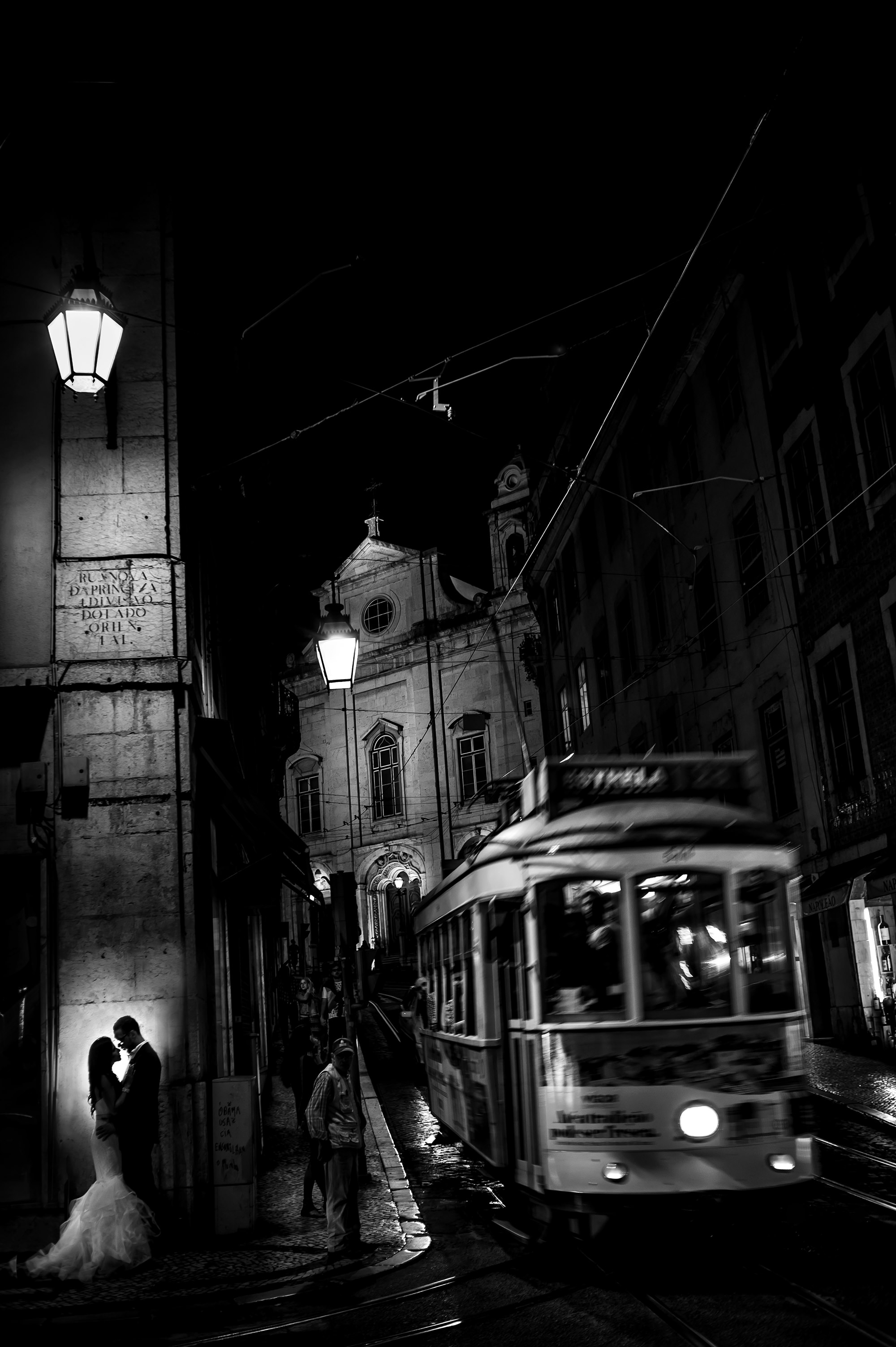Bride and groom on street corner with moving tram - Davina + Daniel