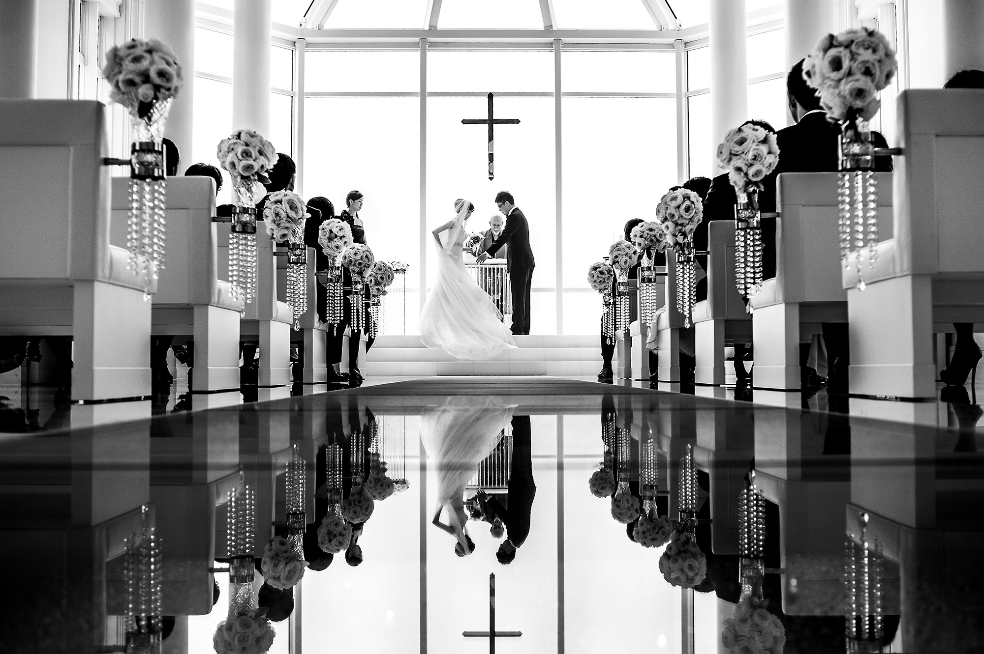 Ceremony with couple and cross reflected in floor - Davina + Daniel