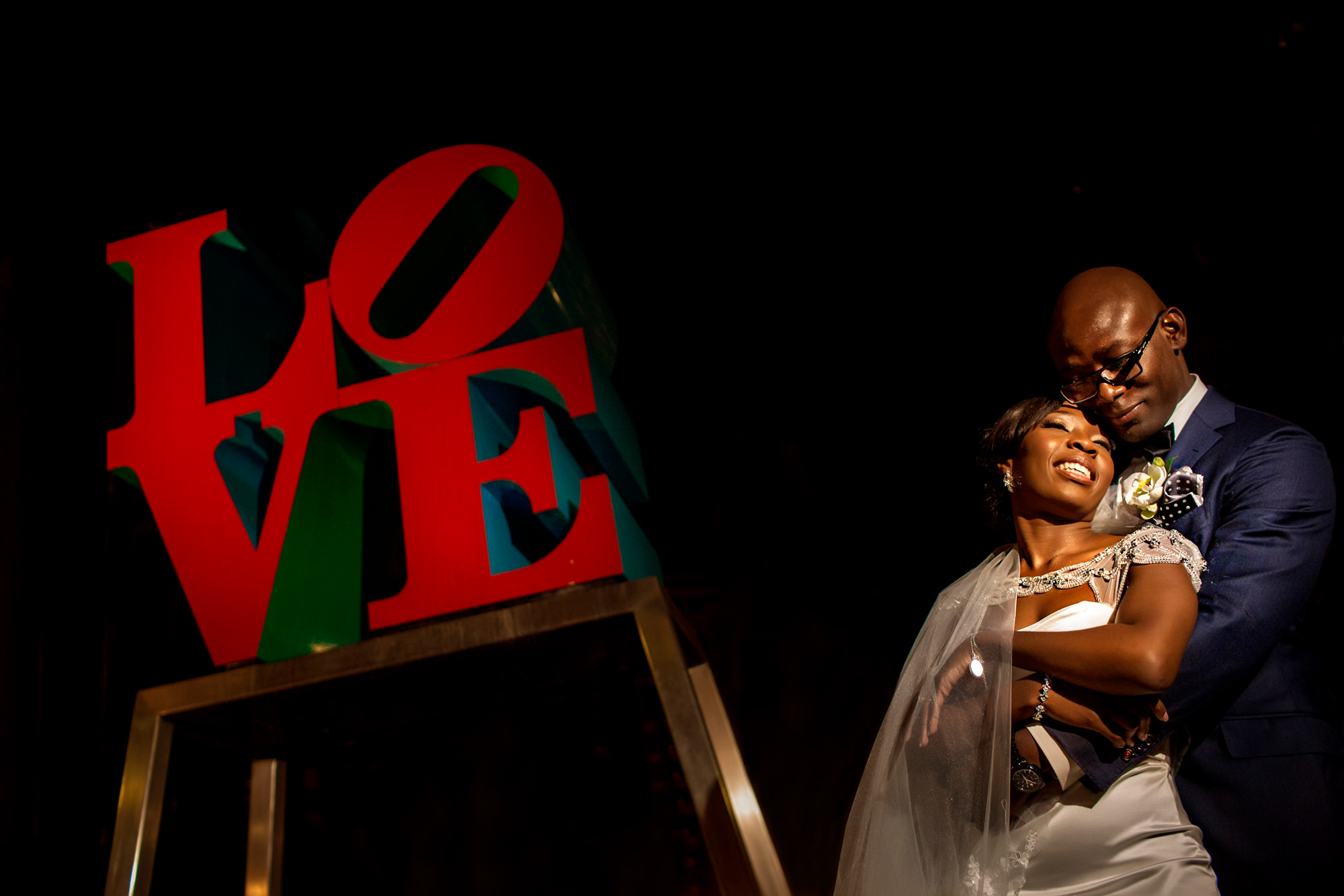 Bride and groom with iconic love sign - photo by Jide Alakija