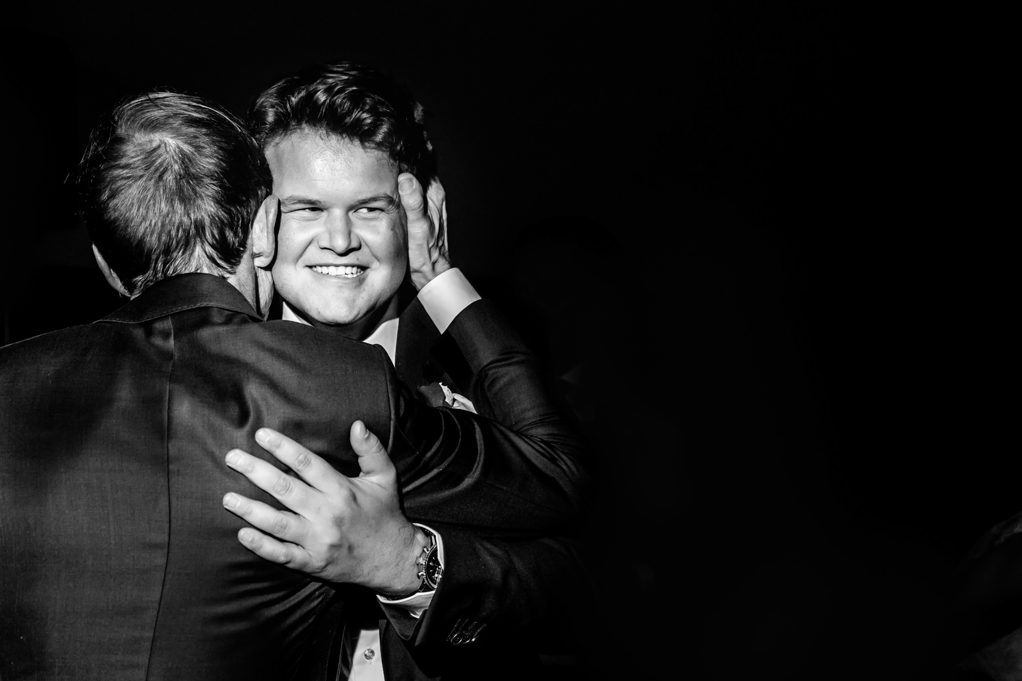 Father hugging groom - photo by Phillipe Swiggers